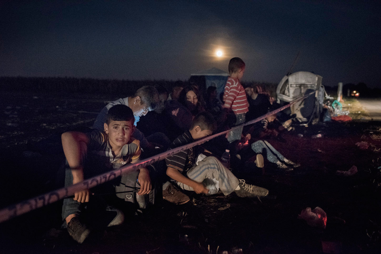Migrants wait behind a police line for Hungarian authorities to register their arrival in the European Union.                               Roszke, Hungary, Aug. 29, 2015.