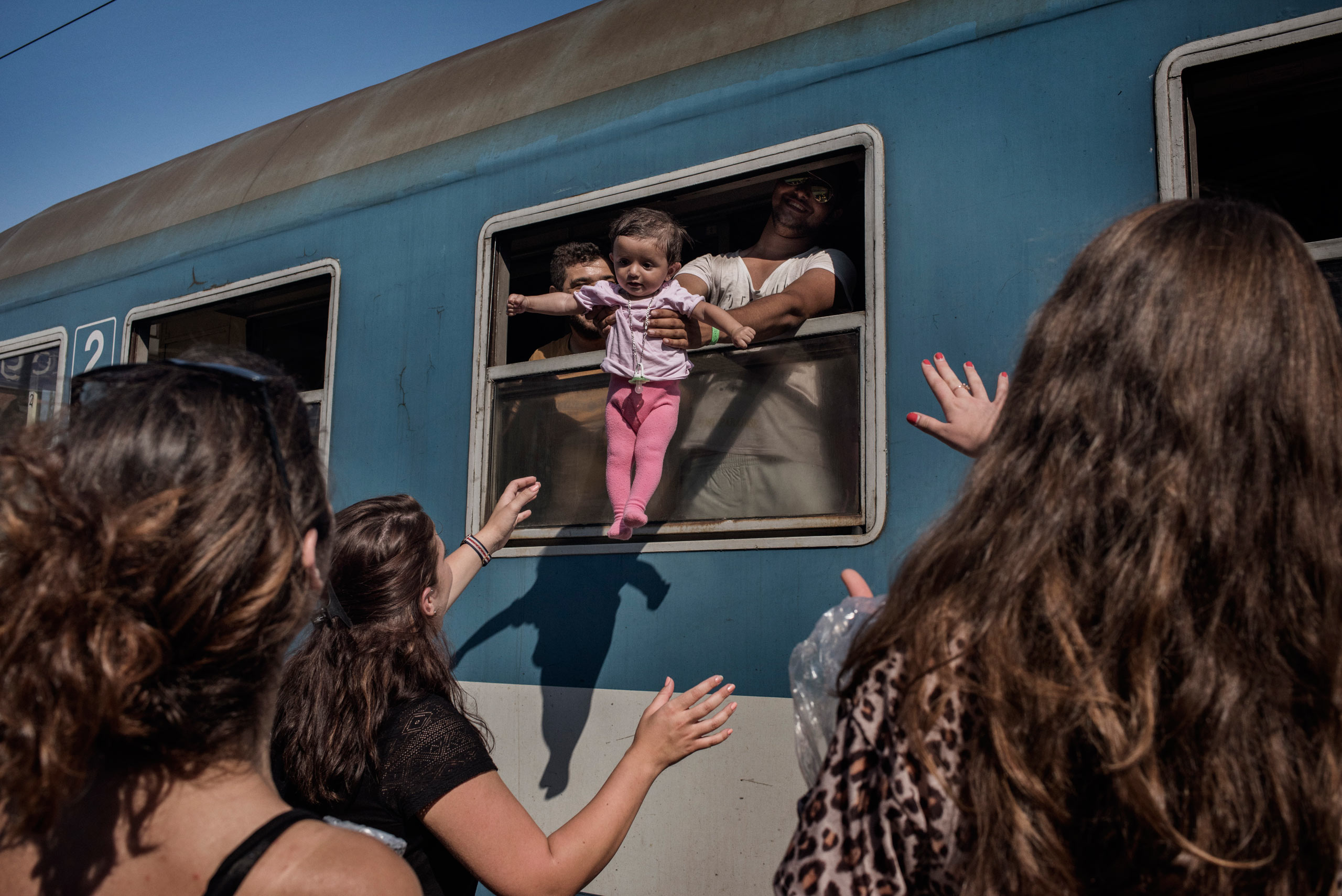 Volunteers wave goodbye to migrants  at the railway station in Szeged, Hungary.                               Hungarian authorities have used passenger trains to transport incoming migrants from the border region to registration centers in other parts of Hungary, Aug. 30, 2015.