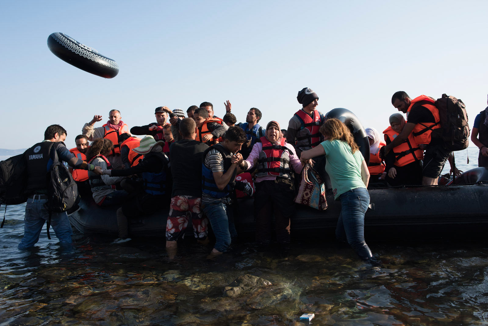 Volunteers from Western Europe help a boat full of migrants from Syria and Afghanistan come ashore on the Greek island of Lesbos, Greece, Sept. 4, 2015.