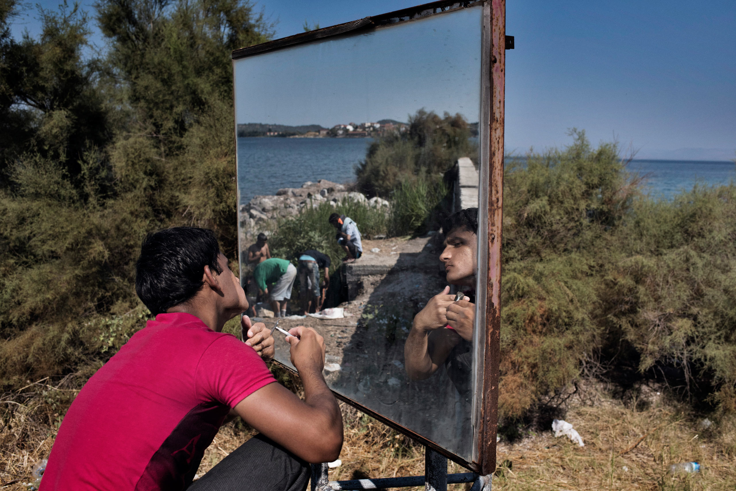 An Afghan migrant shaves with the help of a traffic mirror on the side of a highway on the  Greek island of Lesbos, Greece, Sept. 5, 2015.