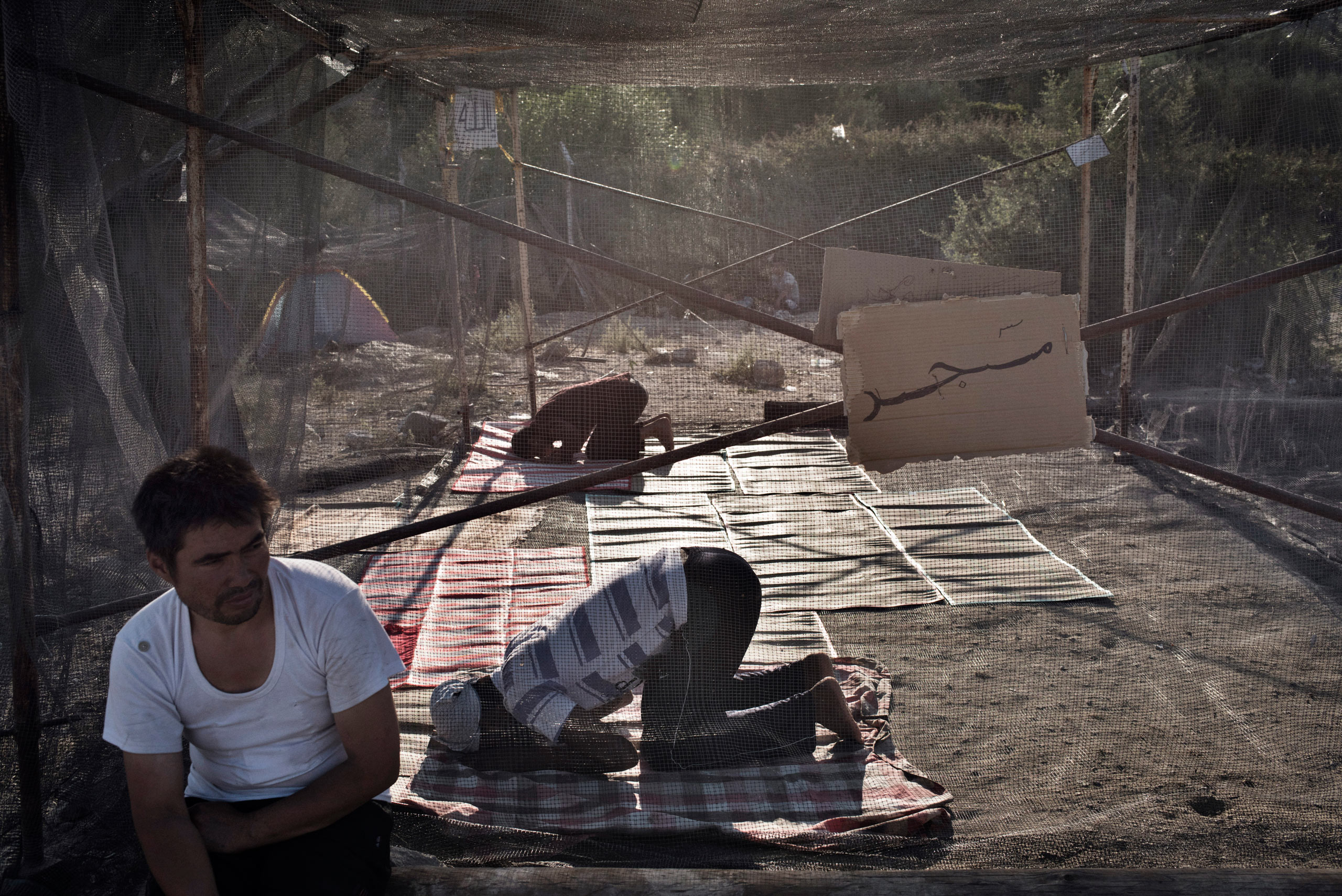 Migrants pray at the makeshift mosque they have built inside a detention and processing camp for asylum seekers on the Greek island of Lesbos, Sept. 4, 2015.