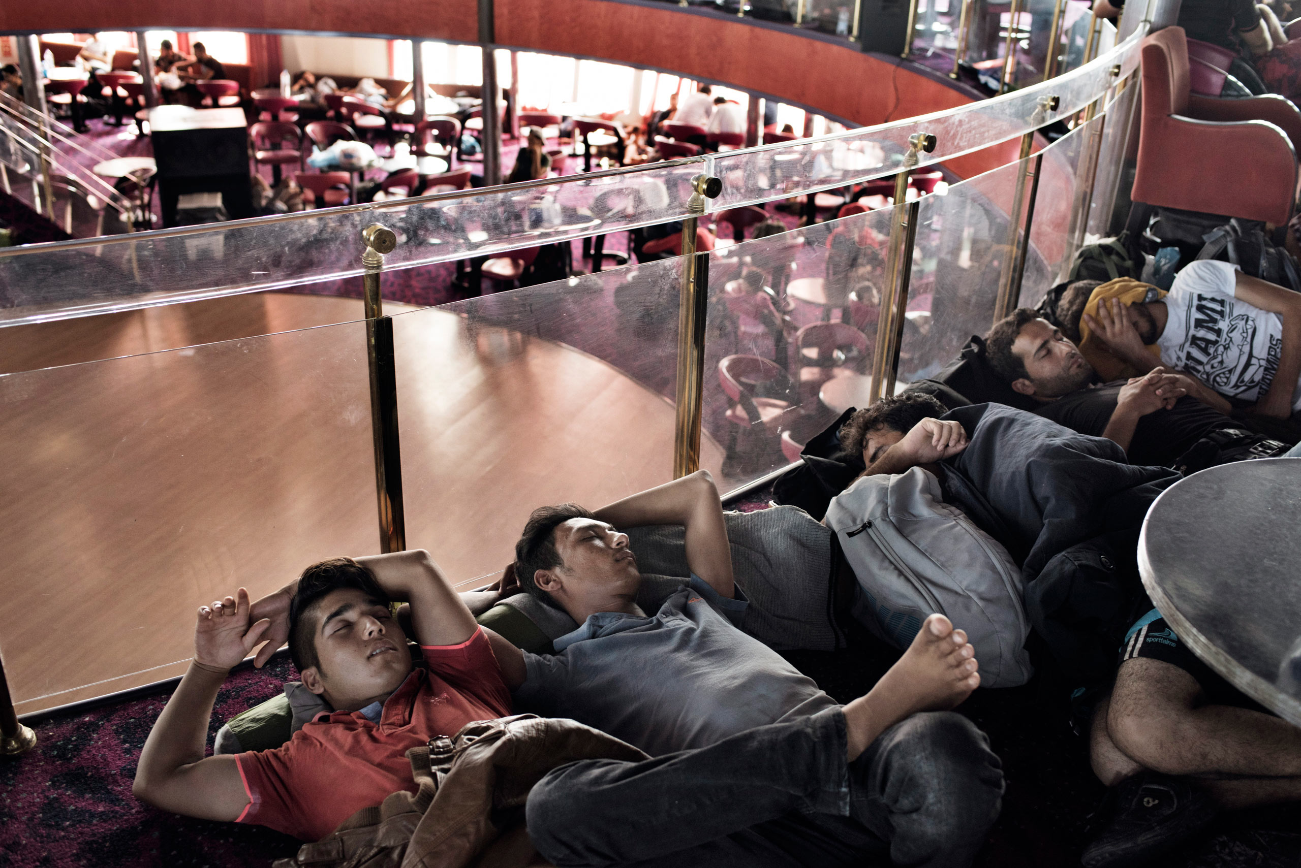 Migrants rest aboard a cruise ship that the Greek government chartered to transport them to Athens from Lesbos. The regular ferry service traveling this route was unable to cope with the unprecedented influx of migrants going through Greece to Western Europe from various conflict zones across the Muslim world. Sept. 5, 2015.