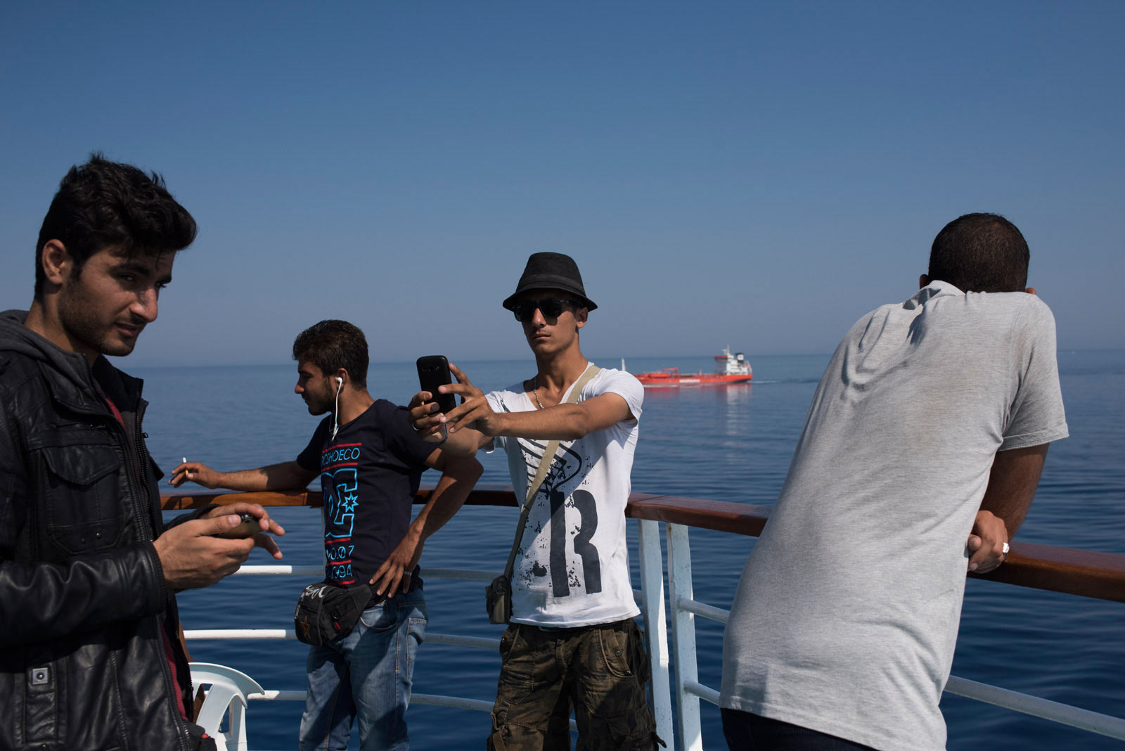 A migrant takes a selfie aboard a cruise ship that the Greek government chartered to transport them to Athens from the Greek island of Lesbos, Sept. 5, 2015.