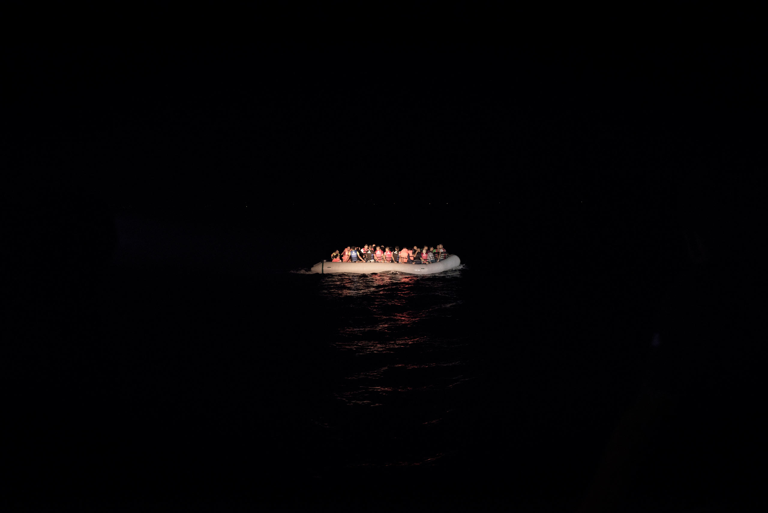 A boat full of migrants, lit by the flashlights from the Greek coast guard, is rescued from the waters near the Greek-Turkish border. Sept. 5, 2015.
