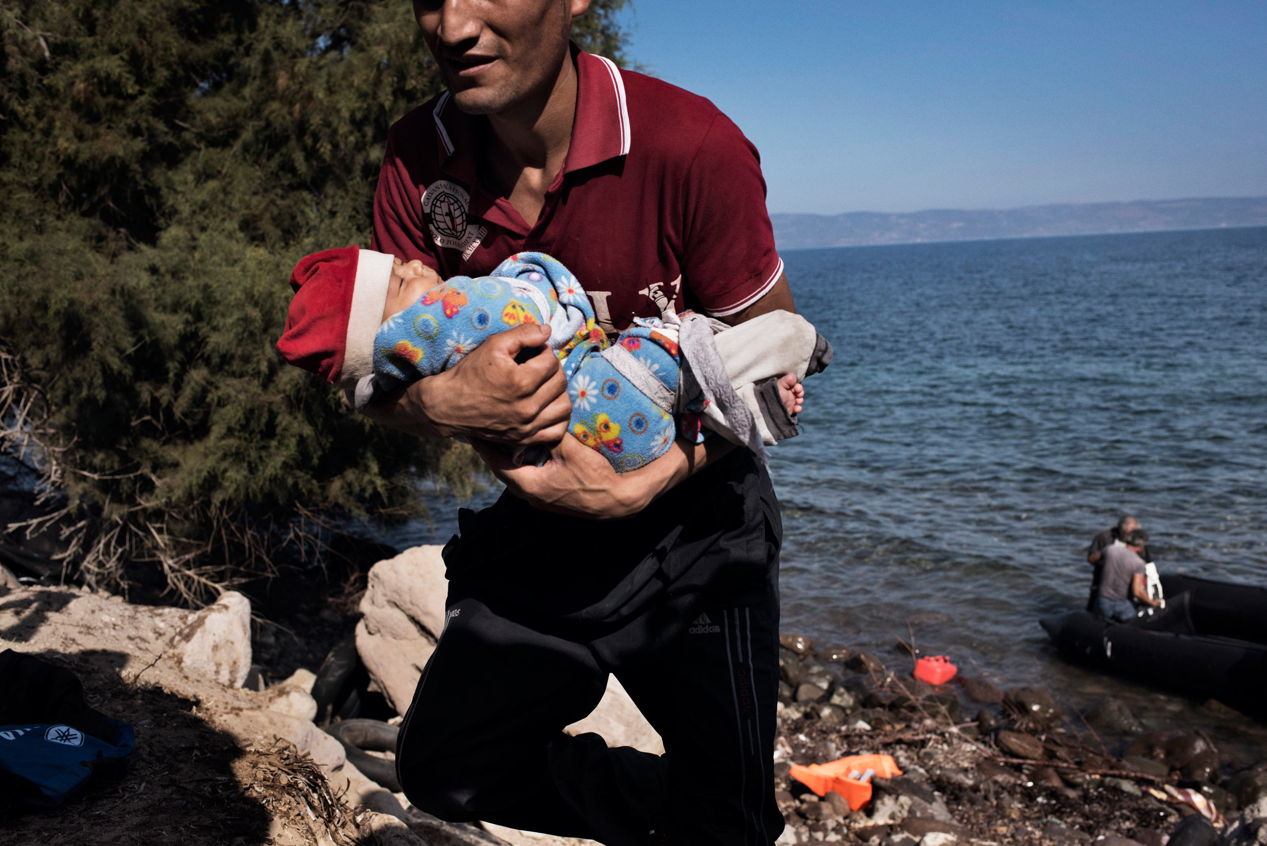 A man holding a child comes ashore near the village of Skala Sikamineas, on the northern tip of Lesbos, after navigating the 6-mile crossing from Turkey on an inflatable raft. The next destination from migrants arriving from Turkey is a 34-mile walk to Mytilini, the capital of Lesbos. Sept. 18, 2015.