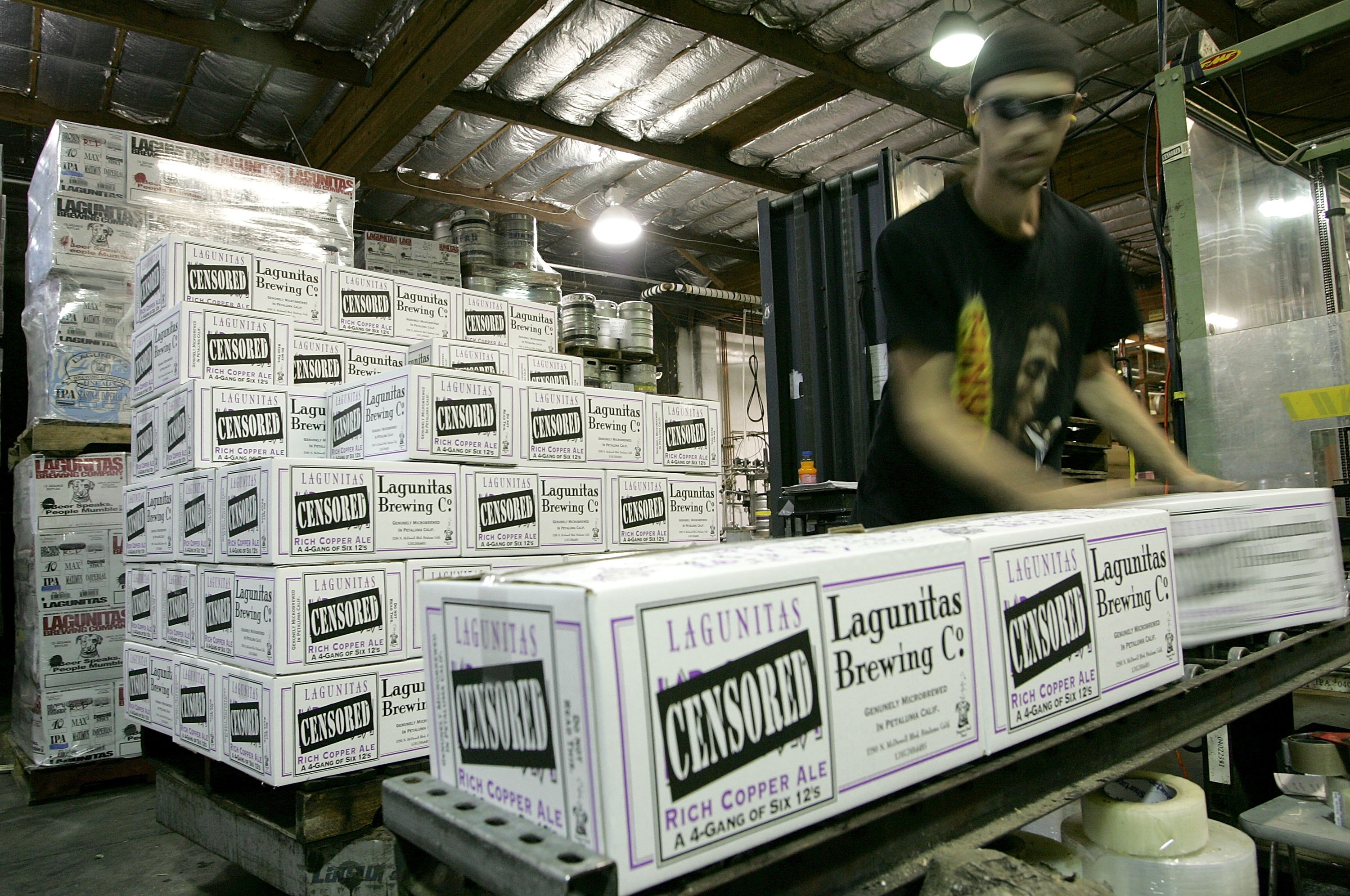 Lagunitas Brewing Company worker Paul Wickham stacks cases of beer at the brewery on March 28, 2006 in Petaluma, Calif.