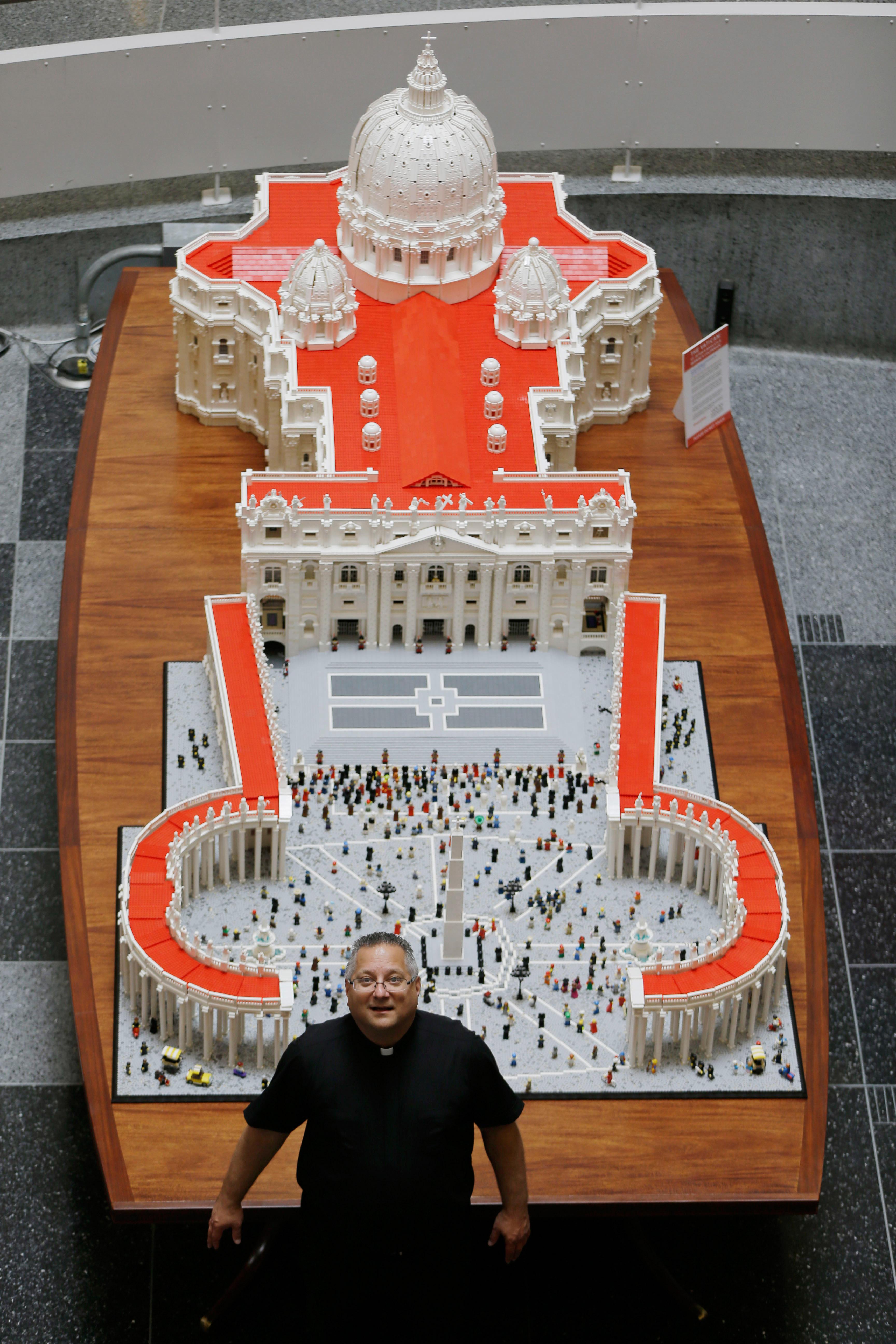 Father Bob Simon poses for a photograph with his creation.