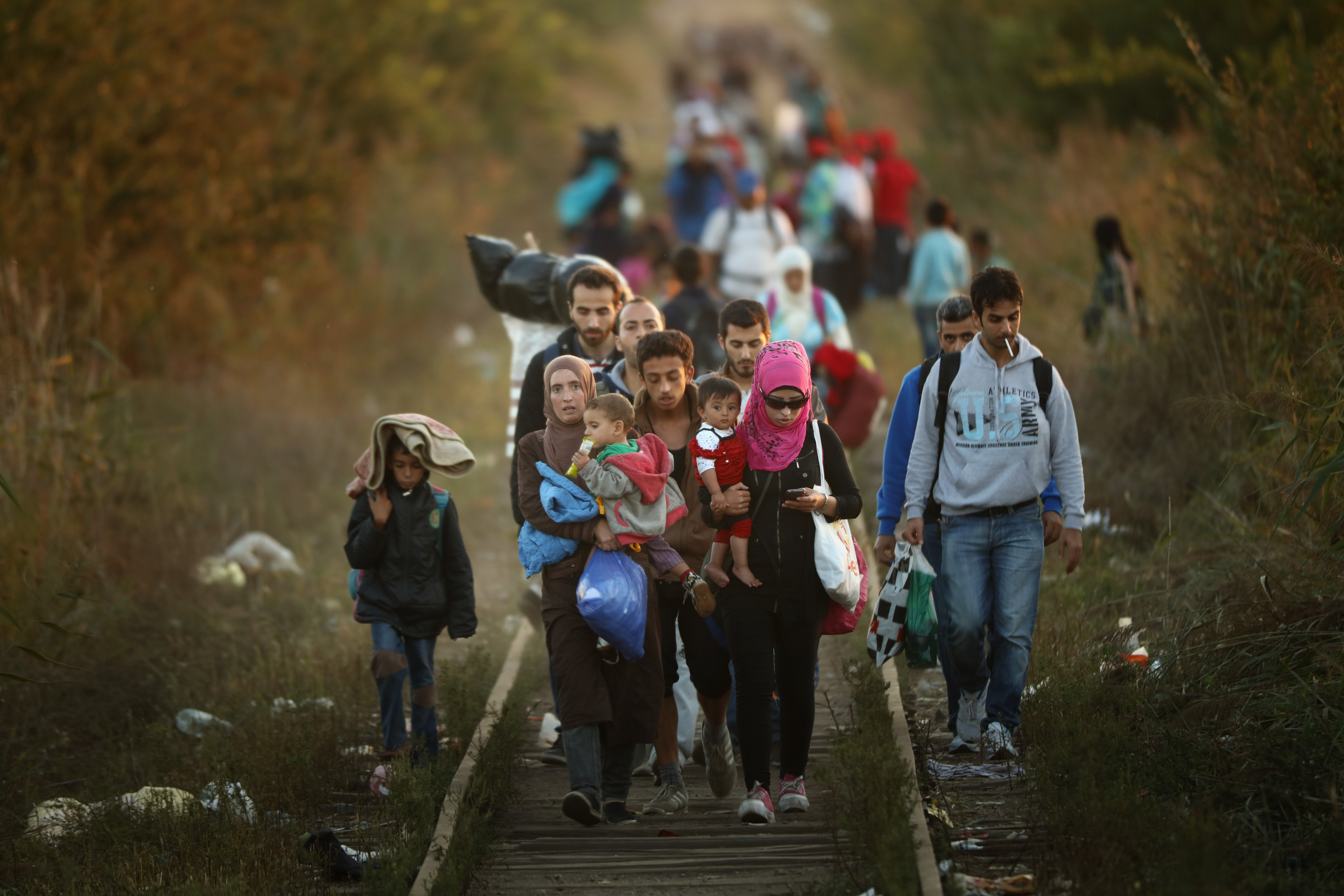 Migrants make their way through Serbia, near the town of Subotica, towards a break in the steel and razor fence erected on the  border by the Hungarian government on Sept. 9, 2015 in Subotica, Serbia.
