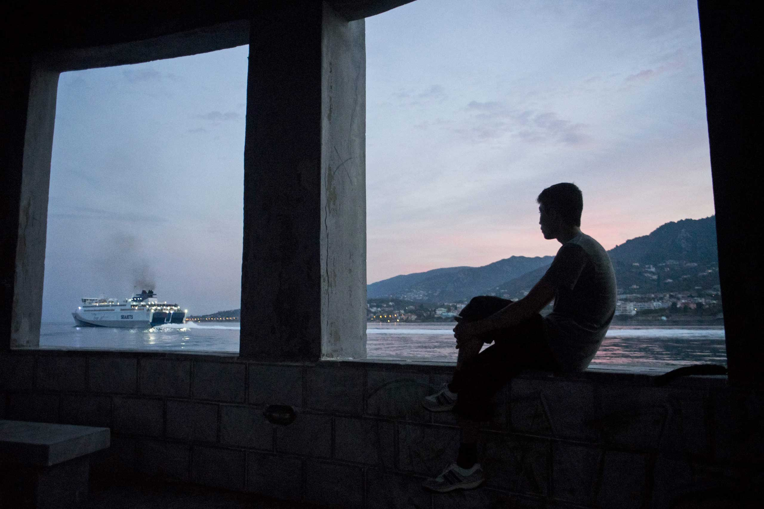 A migrant who recently arrived across the Mediterranean Sea from Turkey, watching a ferry in the port of Mytilene, Lesbos island, Greece, on Oct. 5, 2015.
