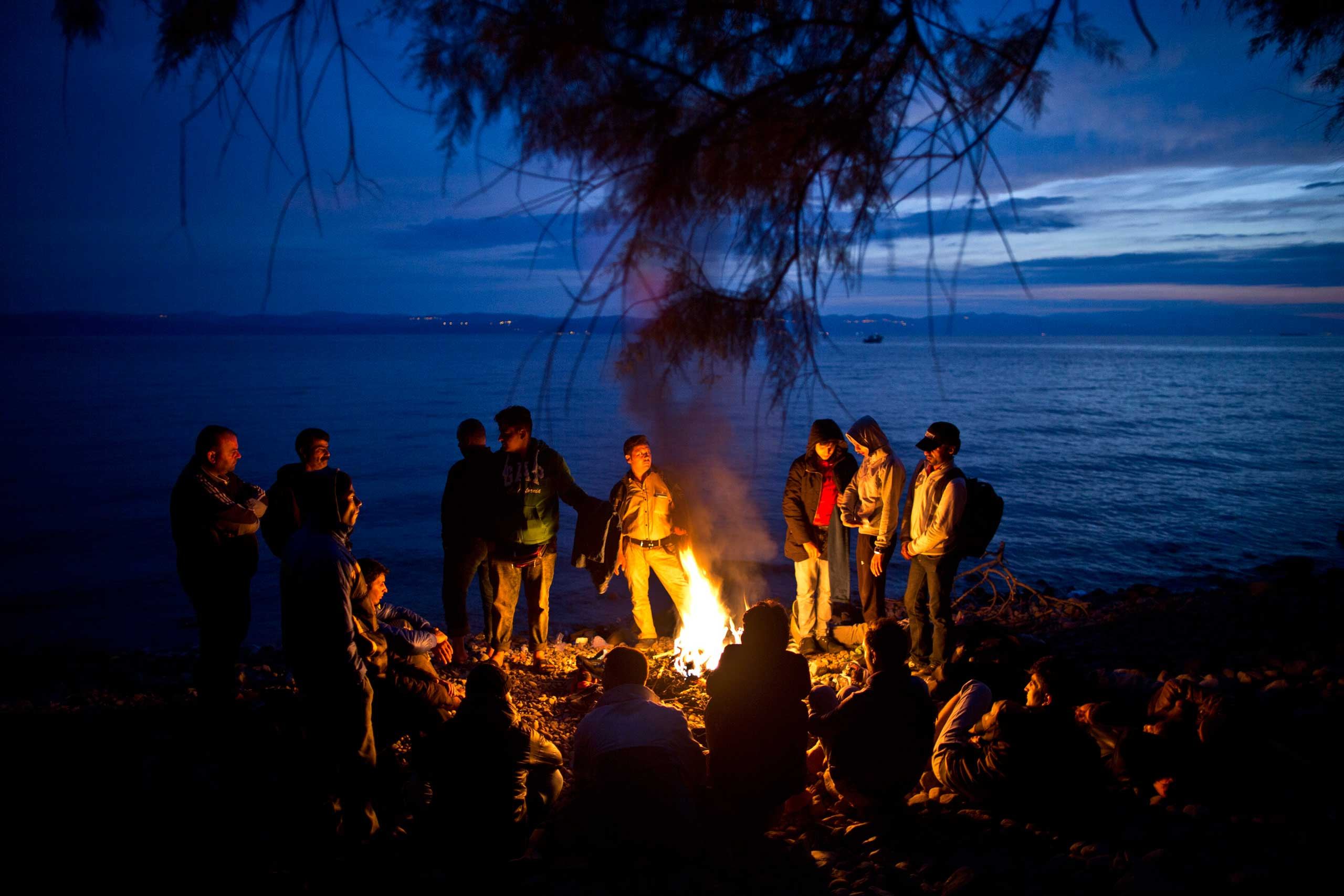Syrian and Afghan refugees warm themselves and dry their clothes around a fire after arriving on a dinghy from the Turkish coast to the northeastern Greek island of Lesbos, early on Oct. 7, 2015.