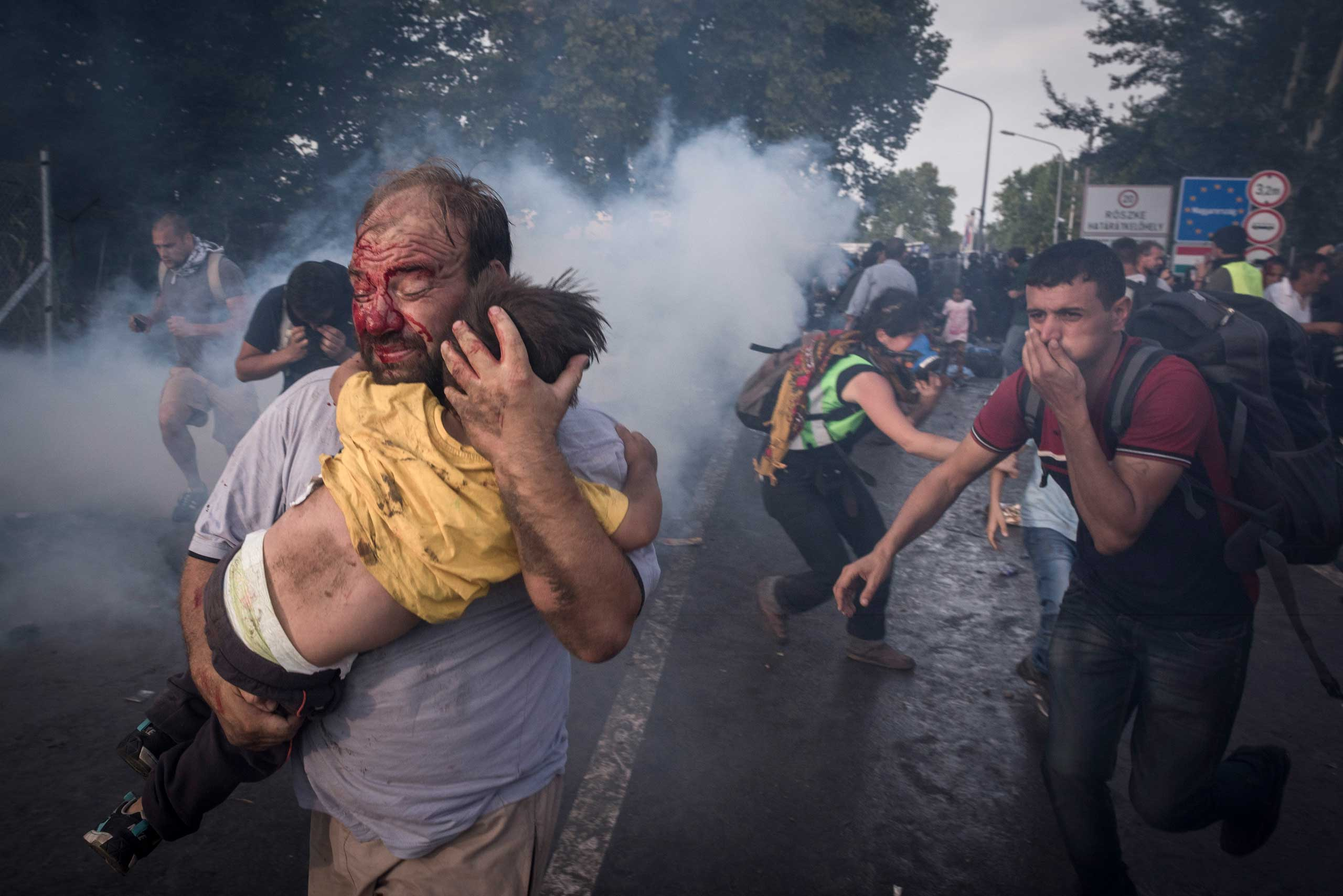 A migrant holds his child during a clash with Hungarian riot police at the Horgos border crossing in Serbia, on Sept. 16, 2015.
