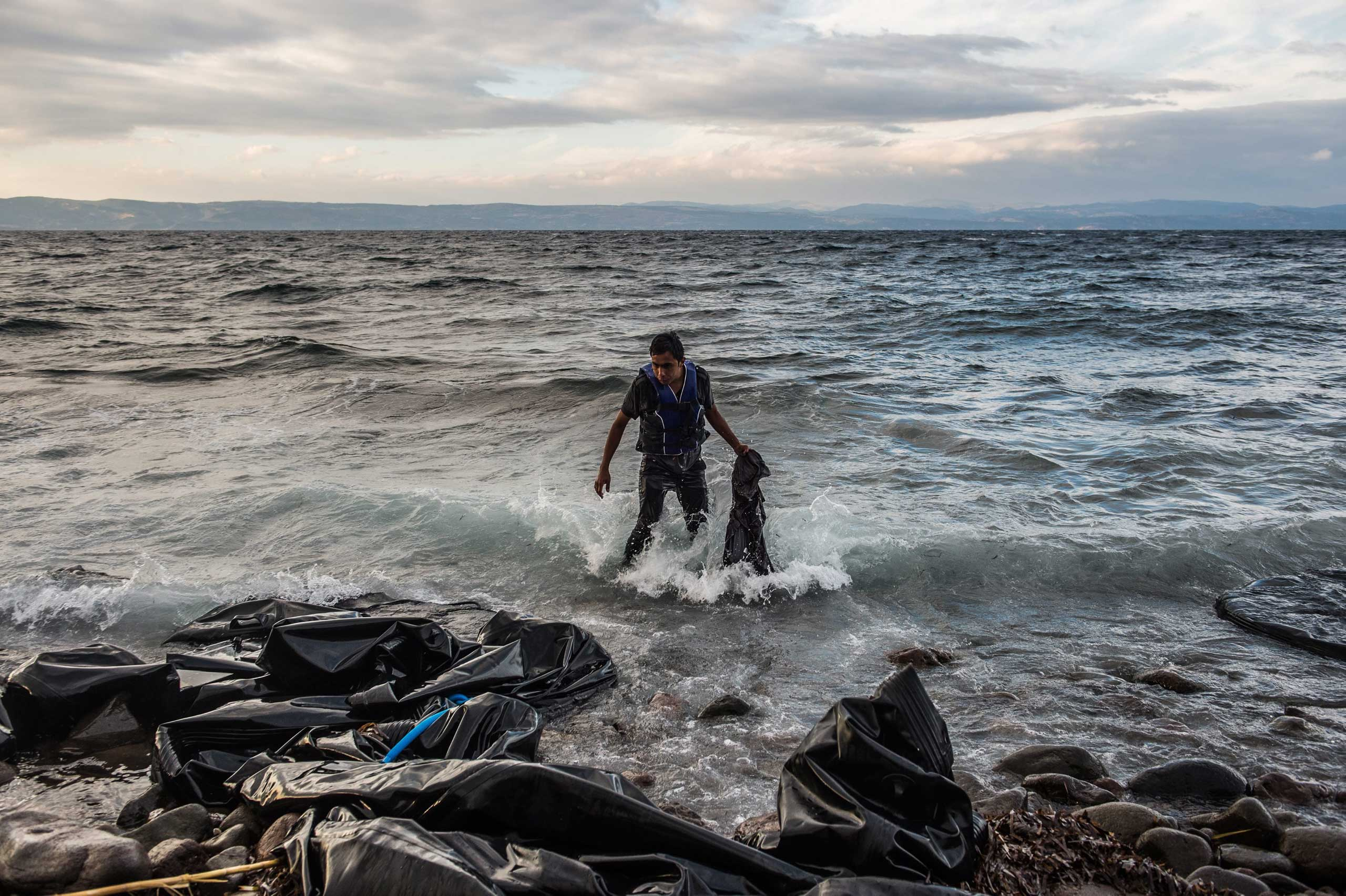 An Afghan wades to the shore after arriving in an overloaded rubber dinghy on the coast near Skala Sikaminias, Lesbos island, Greece, Oct. 1, 2015.