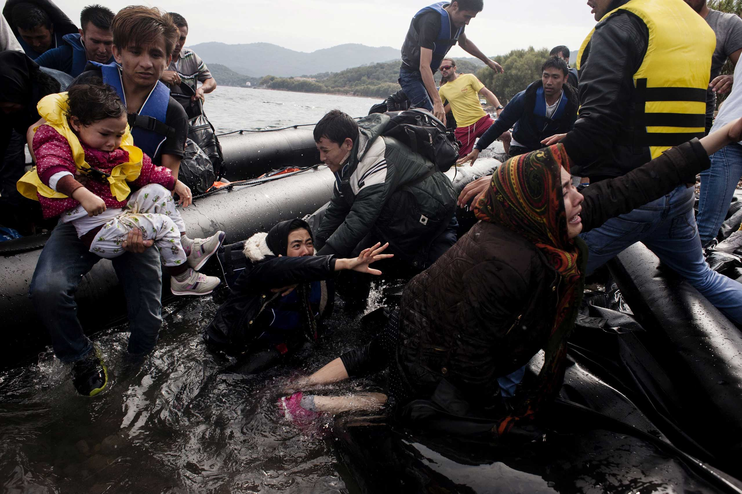Migrants and refugees arrive on Sykamia beach, west of the port of Mytilene, on the Greek island of Lesbos after crossing the Aegean sea from Turkey, on Sept. 22, 2015.