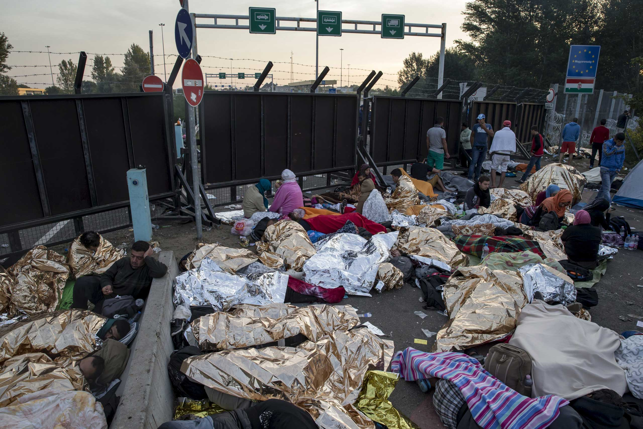 Migrants sleep on a highway in front of a barrier at the border with Hungary near the village of Horgos, Serbia, on Sept. 16, 2015.