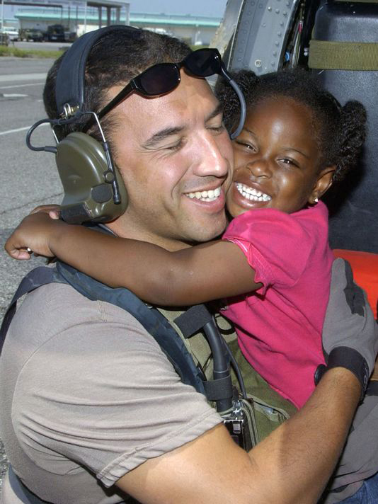 Then Staff Sgt. Mike Maroney hugging three-year-old Lashay Brown after rescuing her in 2005.