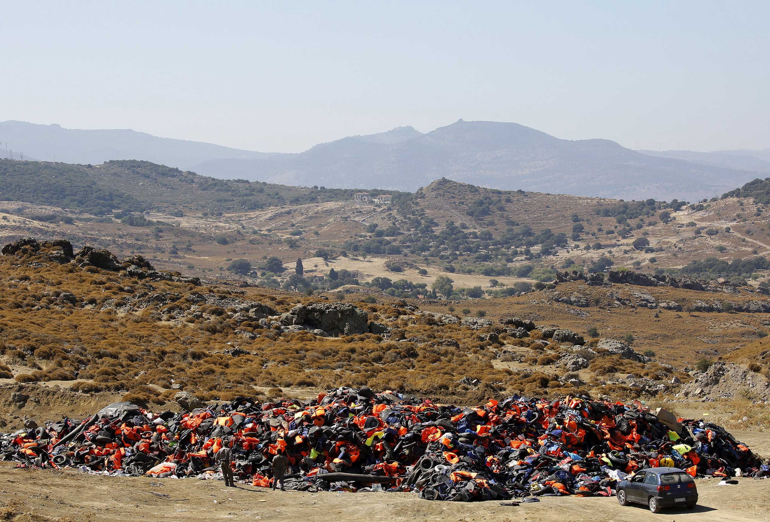 Locals survey a huge pile of deflated dinghies, tubes and life vests left by arriving refugees and migrants on the Greek island of Lesbos, on Sept. 18, 2015.