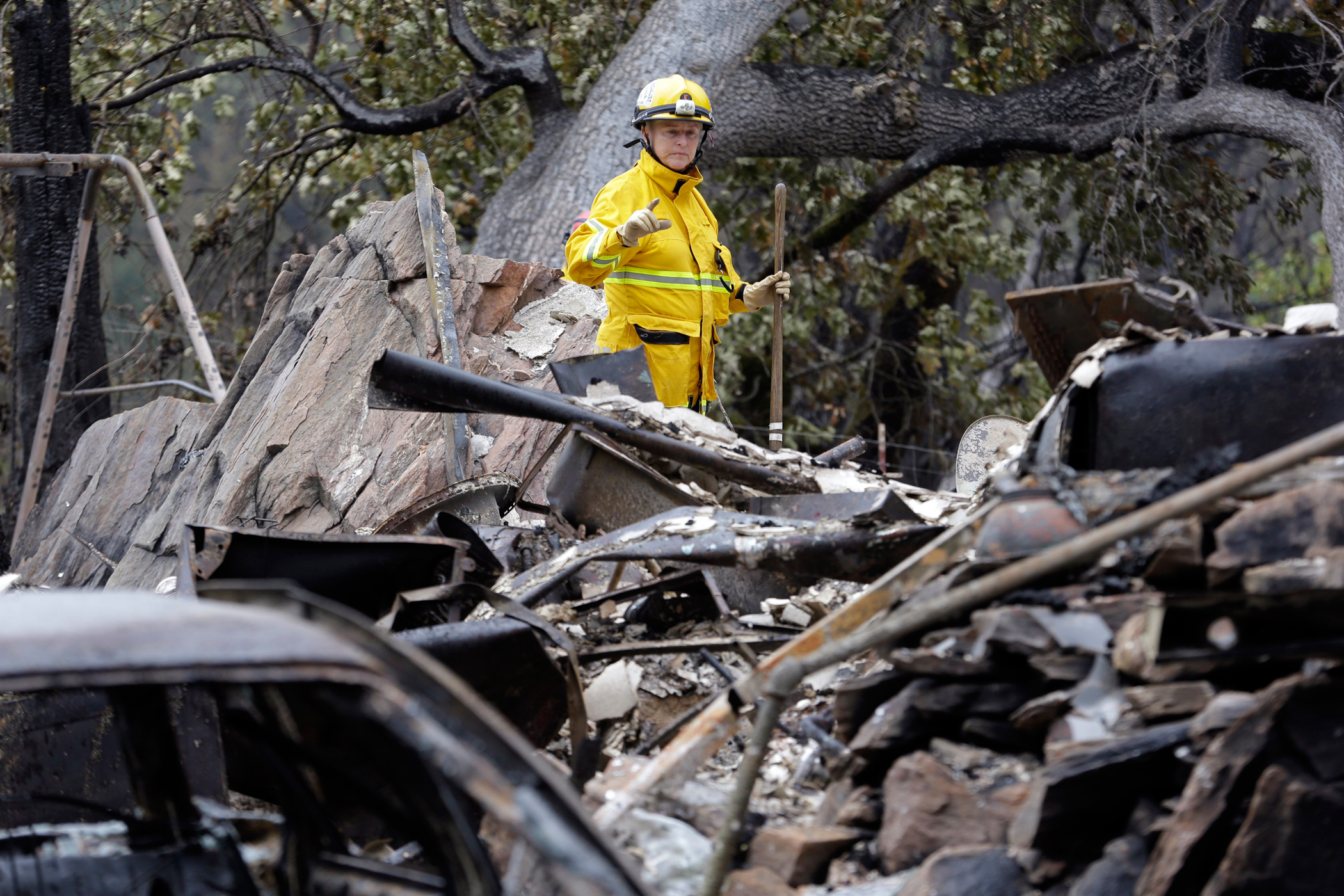 Cadaver search dog handler Lynne Engelbert looks over the remains of a home in the Anderson Springs area of a man missing following a wildfire days earlier on Sept. 16, 2015, near Middletown, Calif.