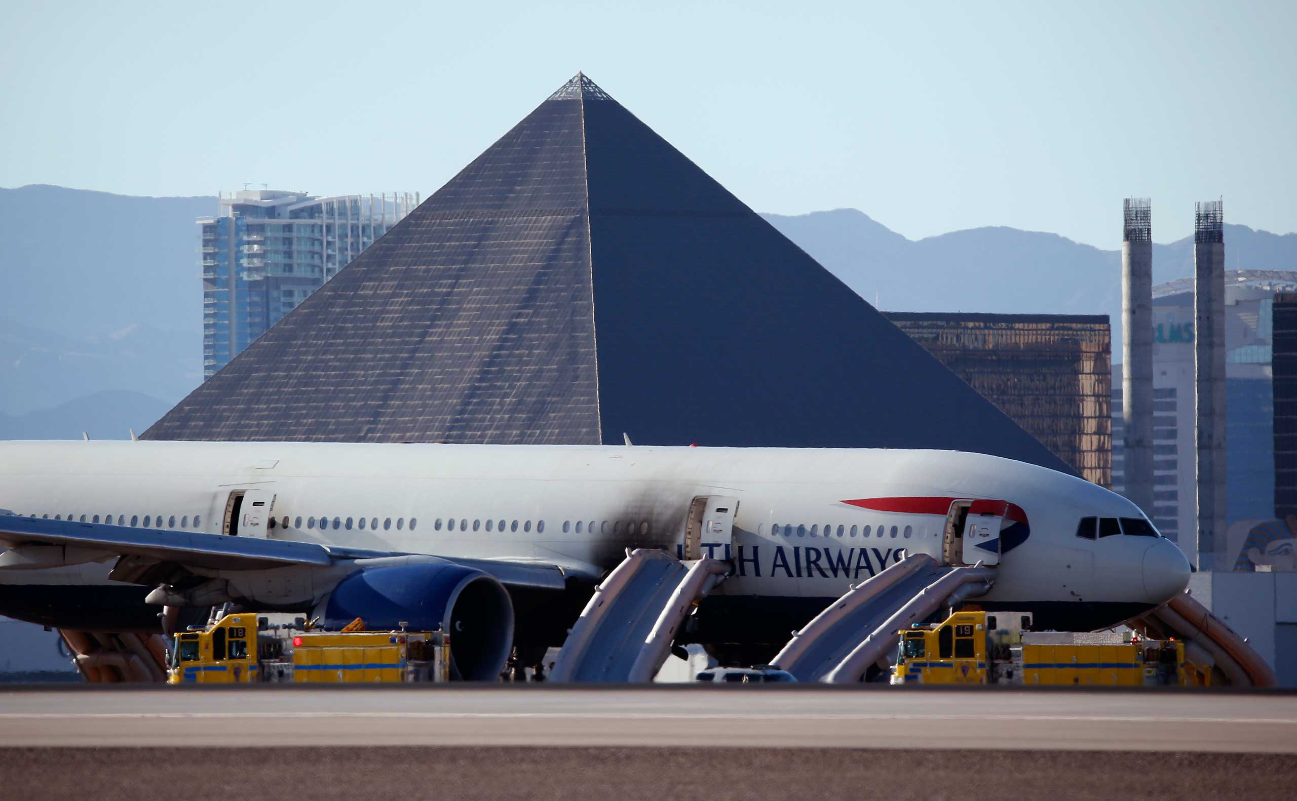 Casinos along the Las Vegas Strip can be seen behind a plane that caught fire at McCarren International Airport , in Las Vegas, on Sept. 8, 2015.