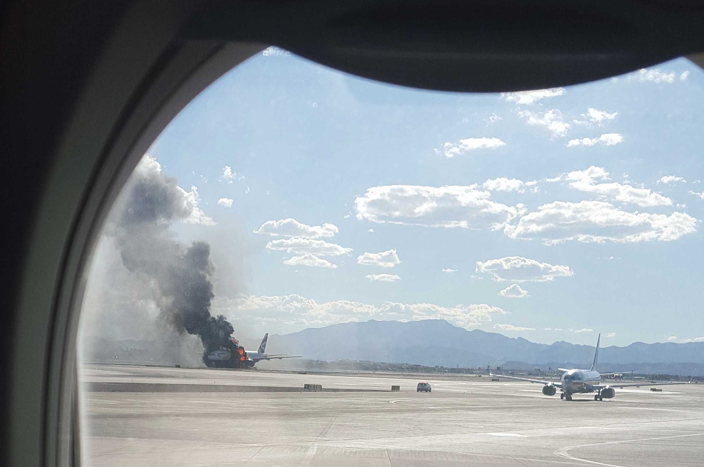 Smoke billows out from a plane that caught fire at McCarren International Airport in Las Vegas, Sept. 8, 2015.