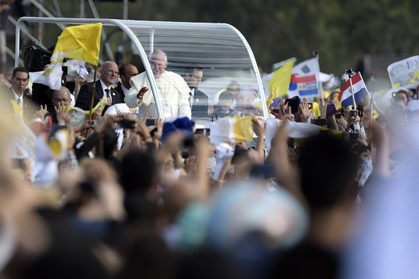 Pope Francis waves as he arrives in the popemobile to deliver a mass at Nu Guazu field in the outskirts of Asuncion, Paraguay on July 12, 2015.