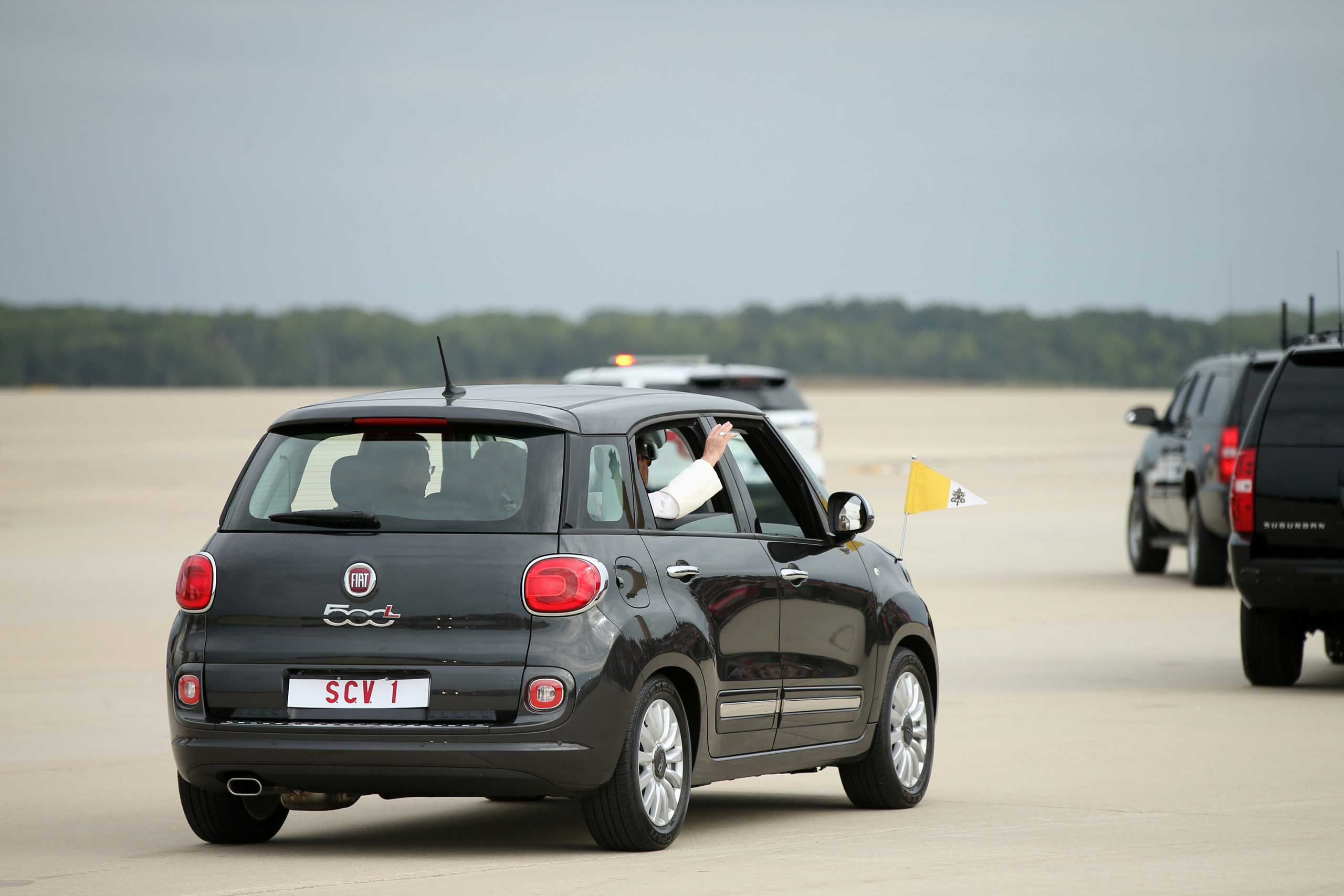 Pope Francis waves from a Fiat 500 as his motorcade departs from Andrews Air Force Base, Md., on Sept. 22, 2015.