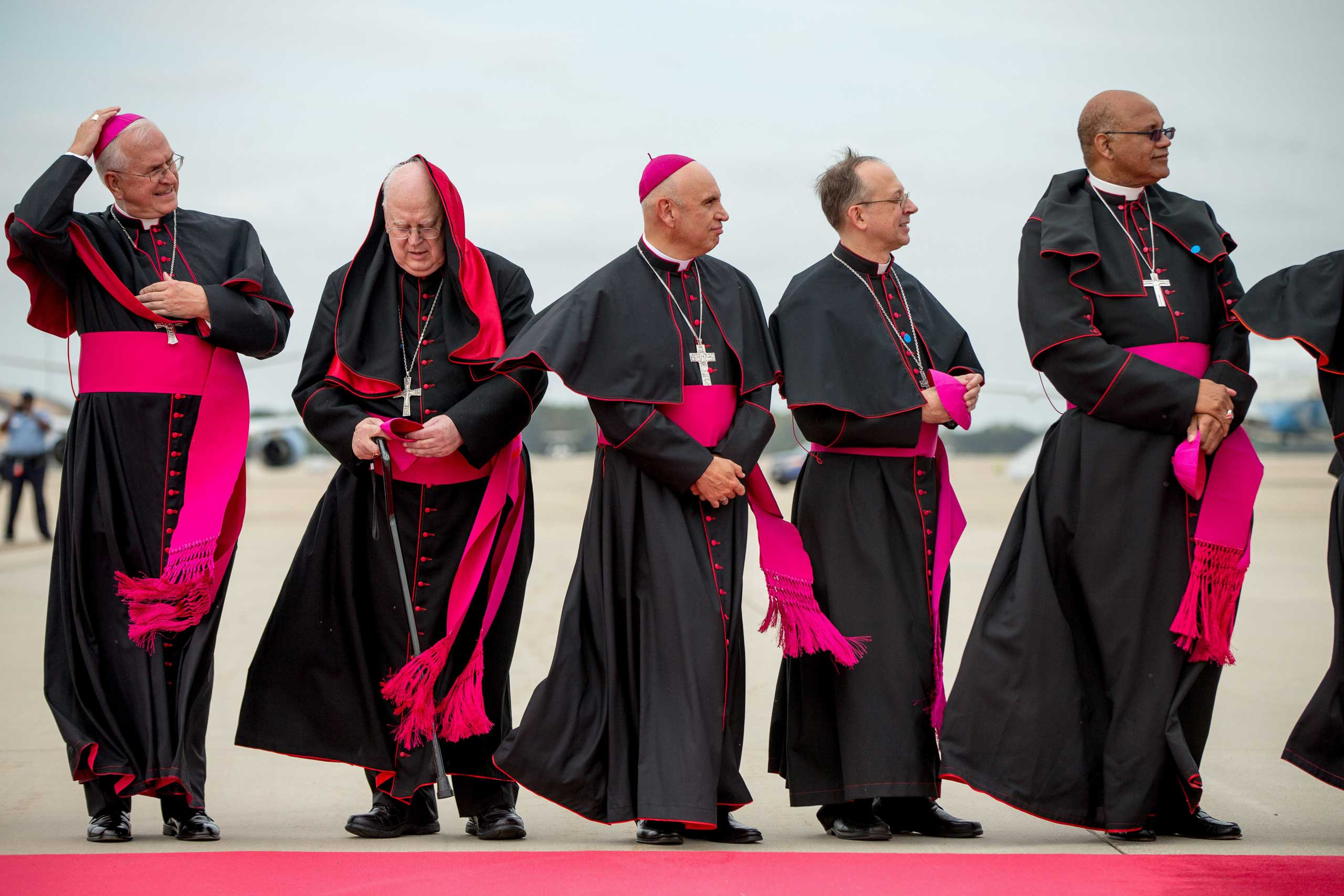 Clergy brace for the wind as they stand along the red carpet on the tarmac at Andrews Air Force Base, Md., on Sept. 22, 2015, as the plane carrying Pope Francis arrives.