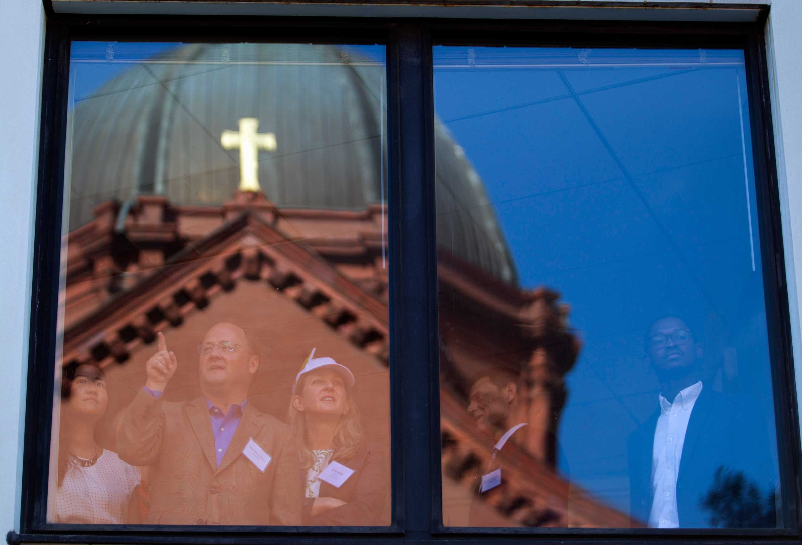 St. Mathews Cathedral is reflected in a nearby building as onlookers wait for Pope Francis to arrive for midday prayer service at St. Matthew's Cathedral in Washington, on Sept. 23, 2015.