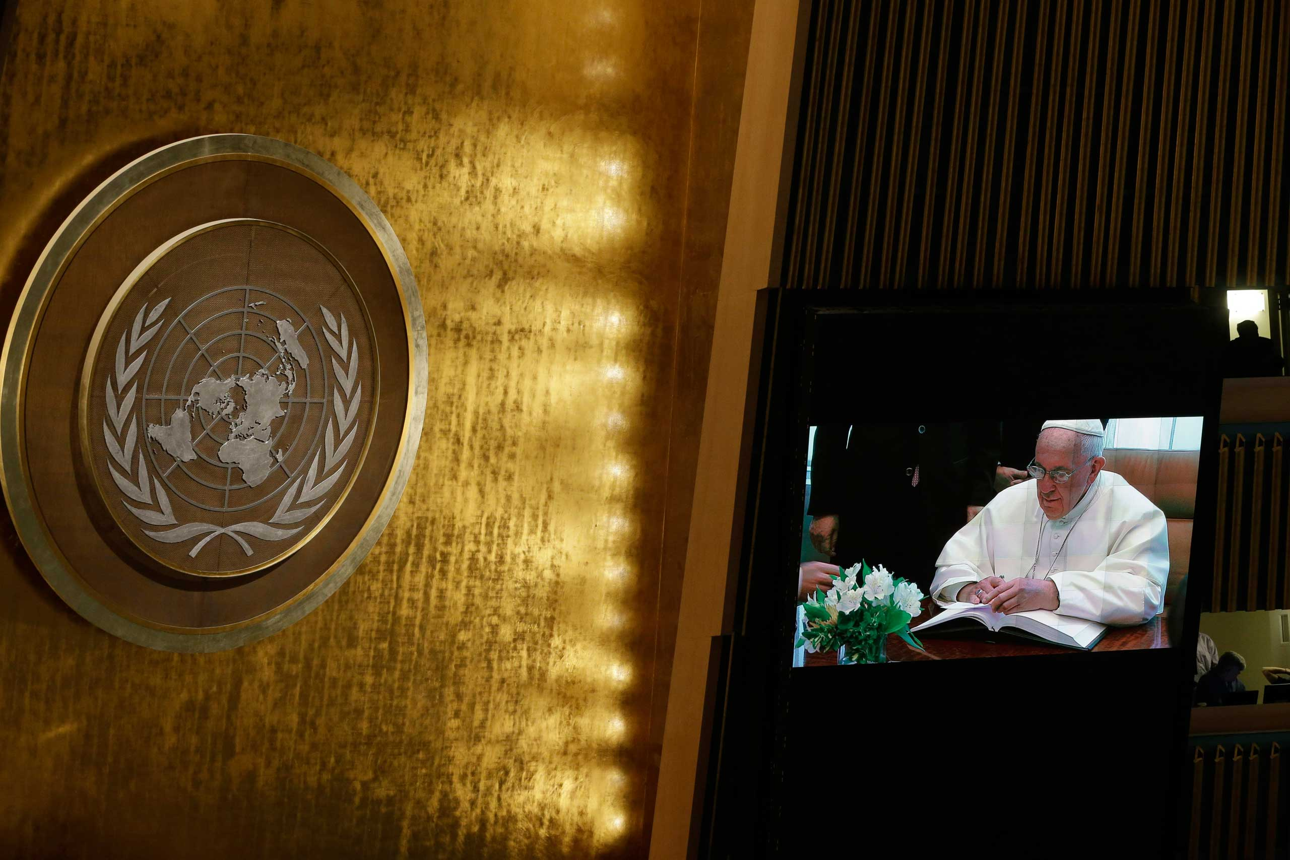 Pope Francis is seen on a video monitor as he signs the United Nations guest book before addressing the General Assembly at United Nations headquarters in New York City, on Sept. 25, 2015.