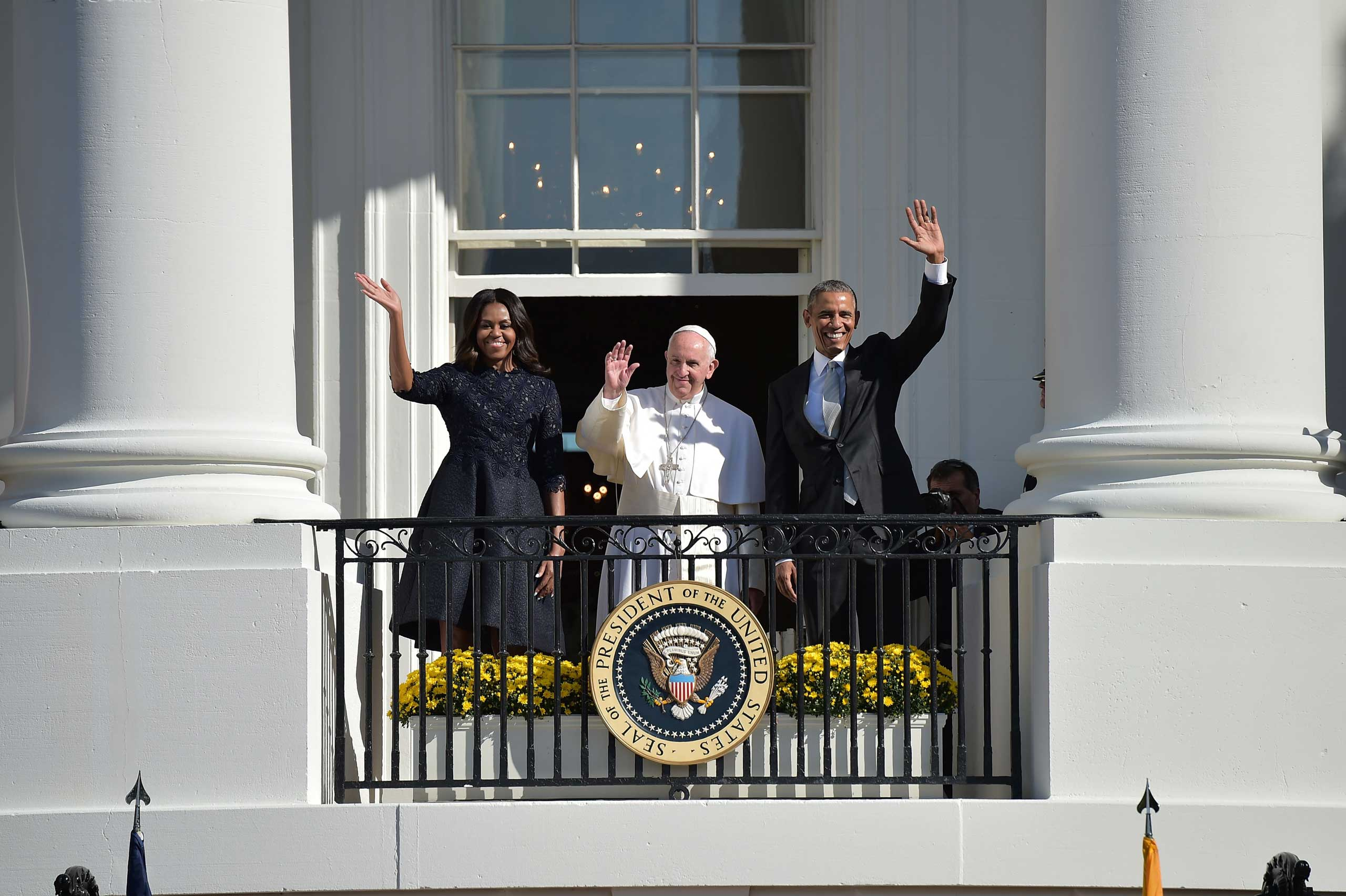 First Lady Michelle Obama, President Barack Obama, and Pope Francis wave during an arrival ceremony at the White House in Washington, on Sept. 23, 2015.