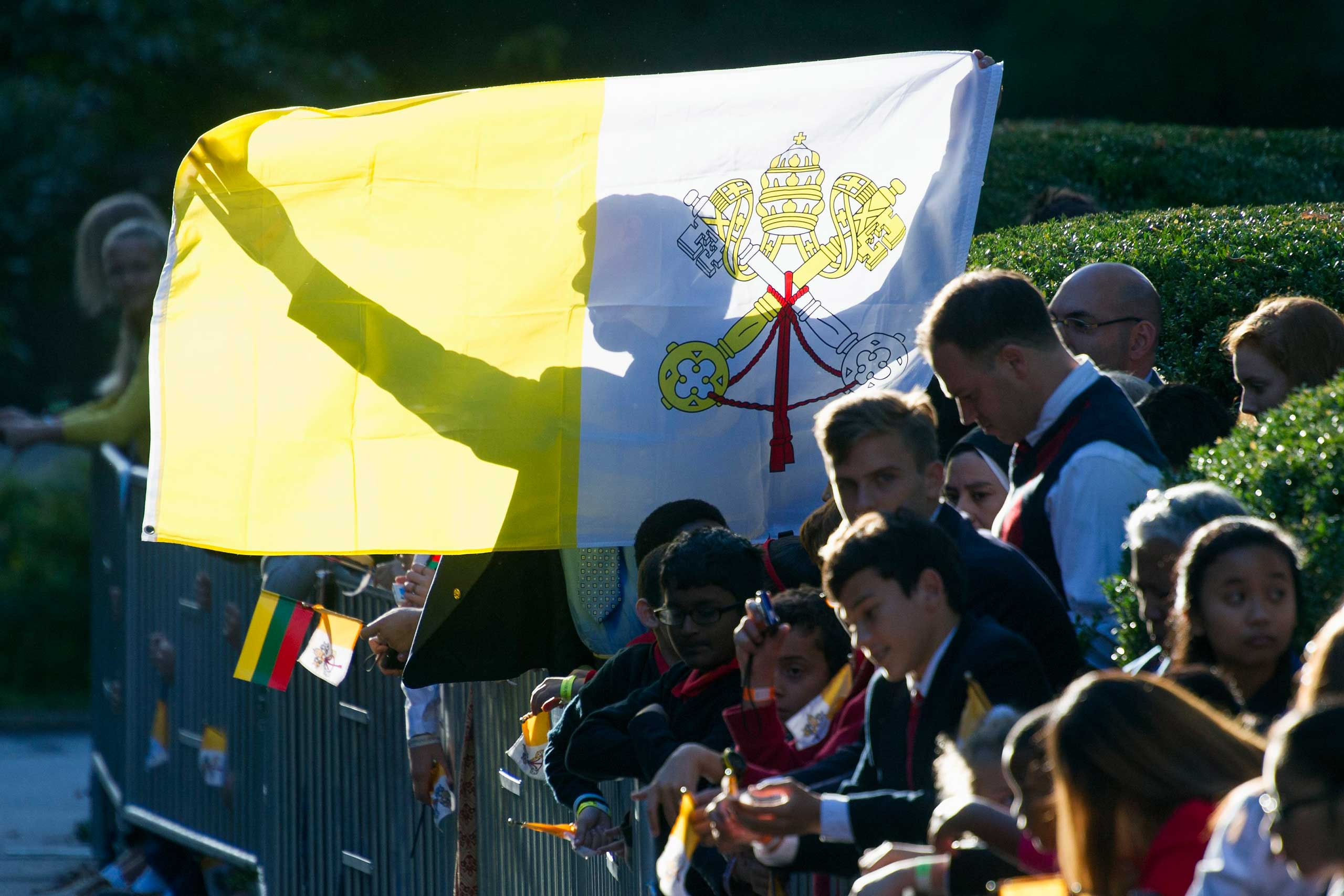 A man holds up a Papal flag as he waits for Pope Francis departure from the Apostolic Nunciature, the Vatican's diplomatic mission in Washington, on Sept. 23, 2015.