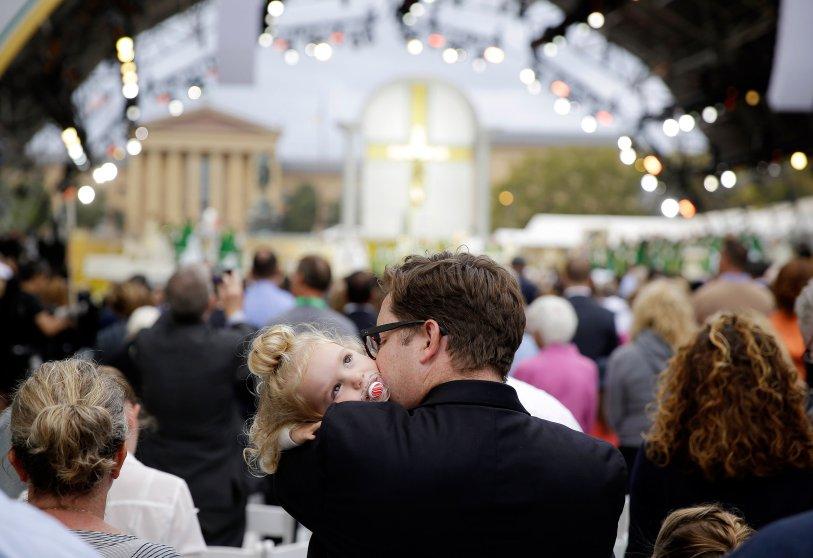 A man holds a child as Pope Francis celebrates Mass, Sunday, Sept. 27, 2015, in Philadelphia. (AP Photo/Matt Slocum)