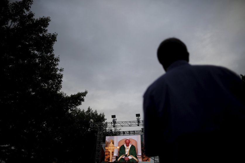 A man looks at a television screen showing Pope Francis taking a pause as he celebrates mass at the Festival of Families Sunday mass along Benjamin Franklin Parkway in Philadelphia, Pennsylvania