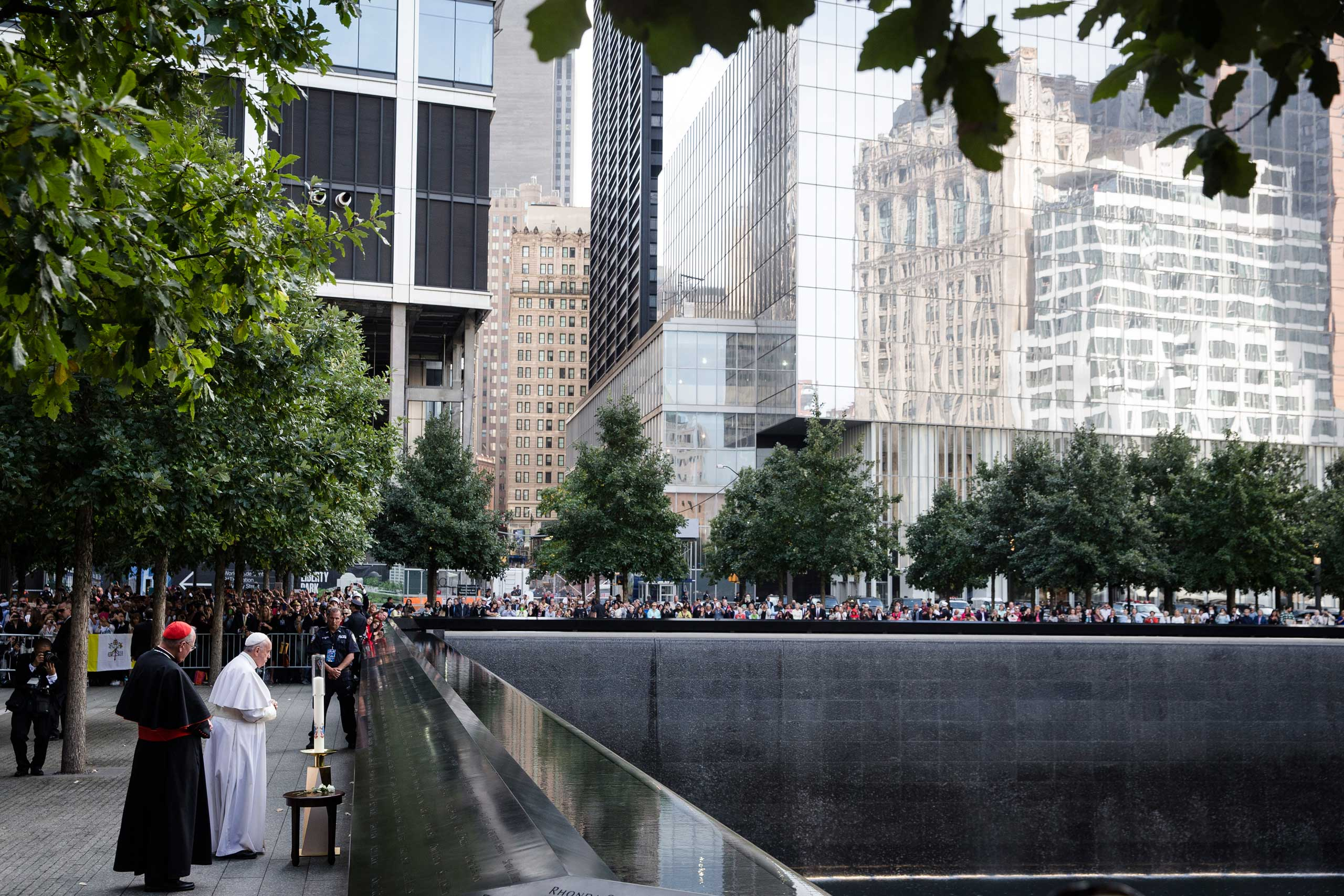 Pope Francis and Cardinal Timothy Dolan, left, pray at the South Pool of the 9/11 Memorial in downtown Manhattan, on Sept. 25, 2015.