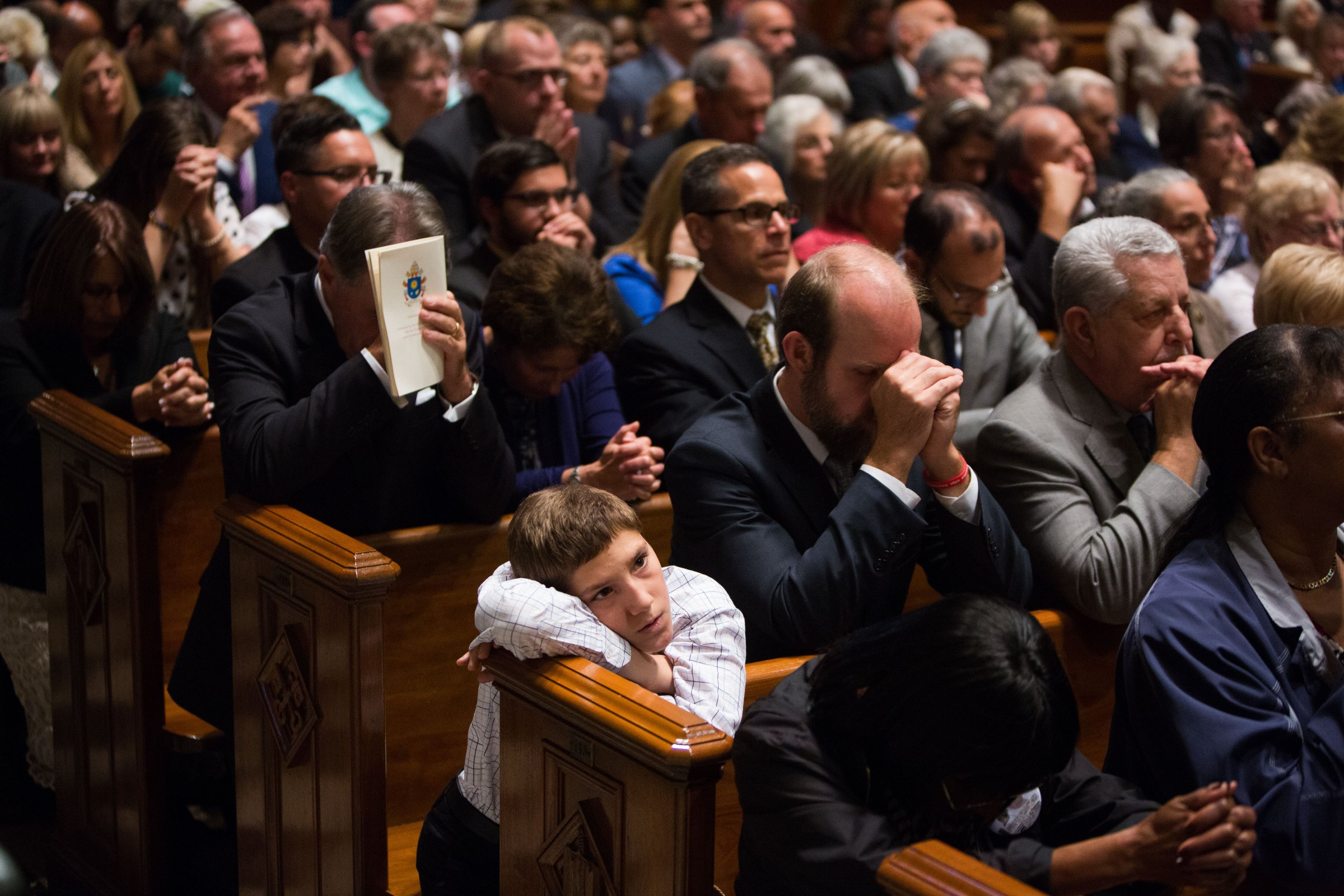 People pray and watch as Pope Francis celebrates mass at the Cathedral Basilica of Saints Peter and Paul in Philadelphia, on Sept. 26, 2015.