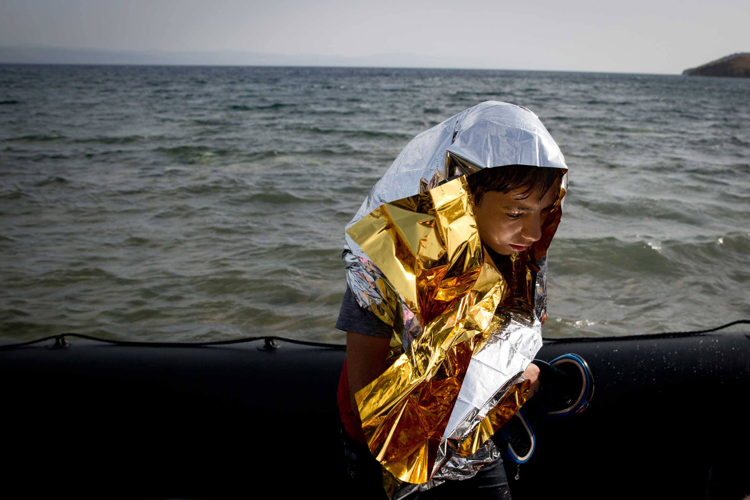 A young Syrian boy is wrapped with a thermal blanket as he arrives with others at the coast on a dinghy after crossing from Turkey, at the island of Lesbos, Greece, on Sept. 7, 2015.