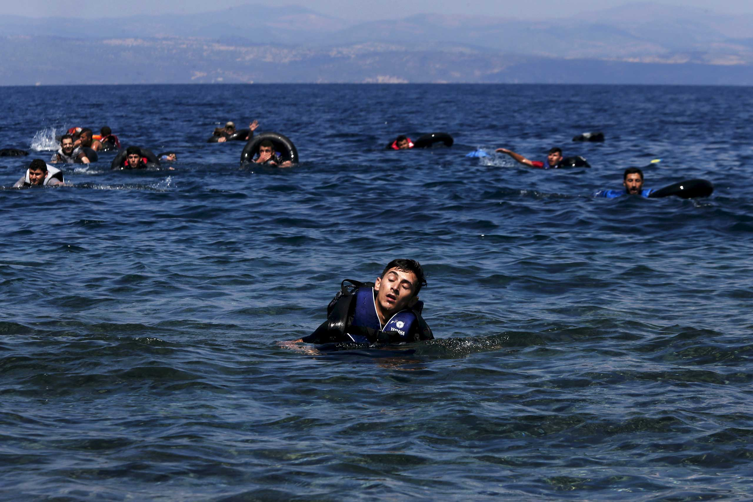 A refugee reacts from exhaustion while swimming towards the shore after a dinghy carrying Syrian and Afghan refugees before reaching the Greek island of Lesbos, on Sept. 13, 2015.