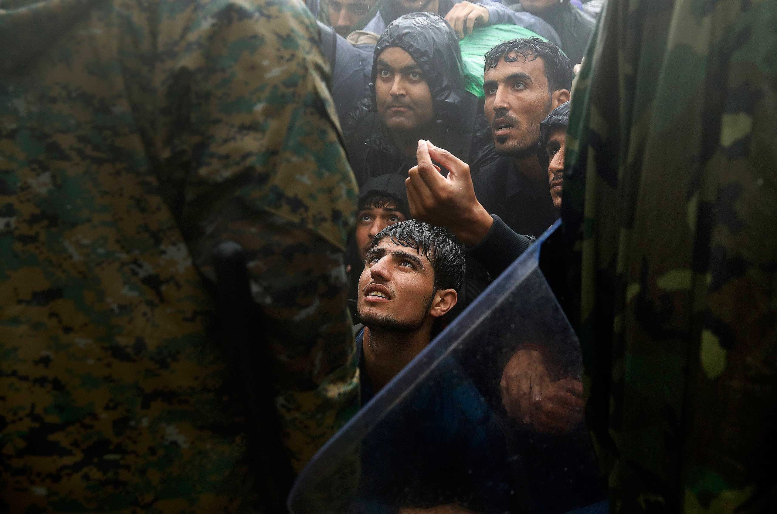 Migrants and refugees beg Macedonian police to allow passage to cross the border from Greece into Macedonia during a rainstorm, near the Greek village of Idomeni, on Sept. 10, 2015.