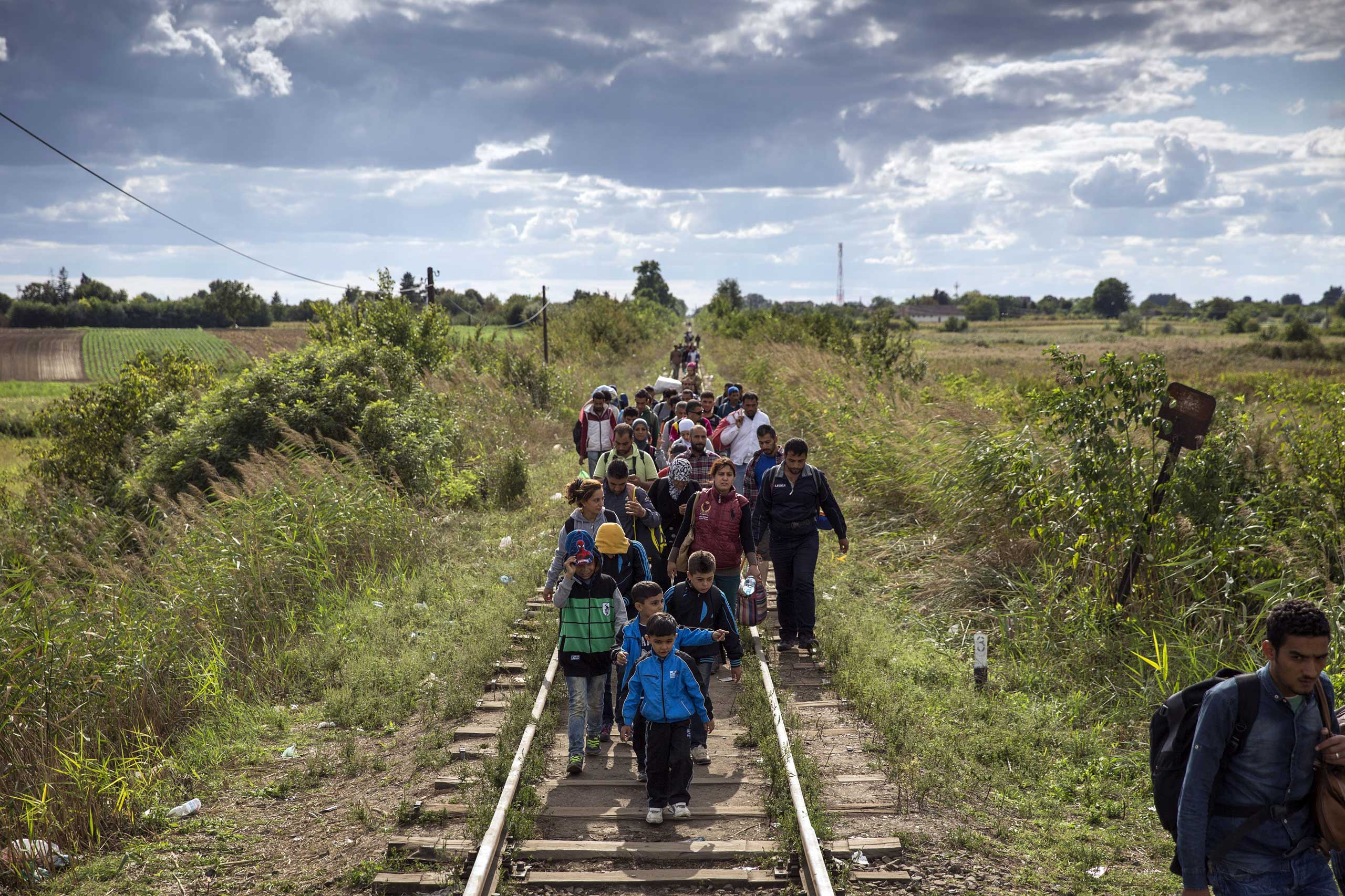Migrants cross into Hungary as they walk over railroad tracks at the Serbian border with Hungary in Horgas, Serbia, on Sept. 7, 2015.