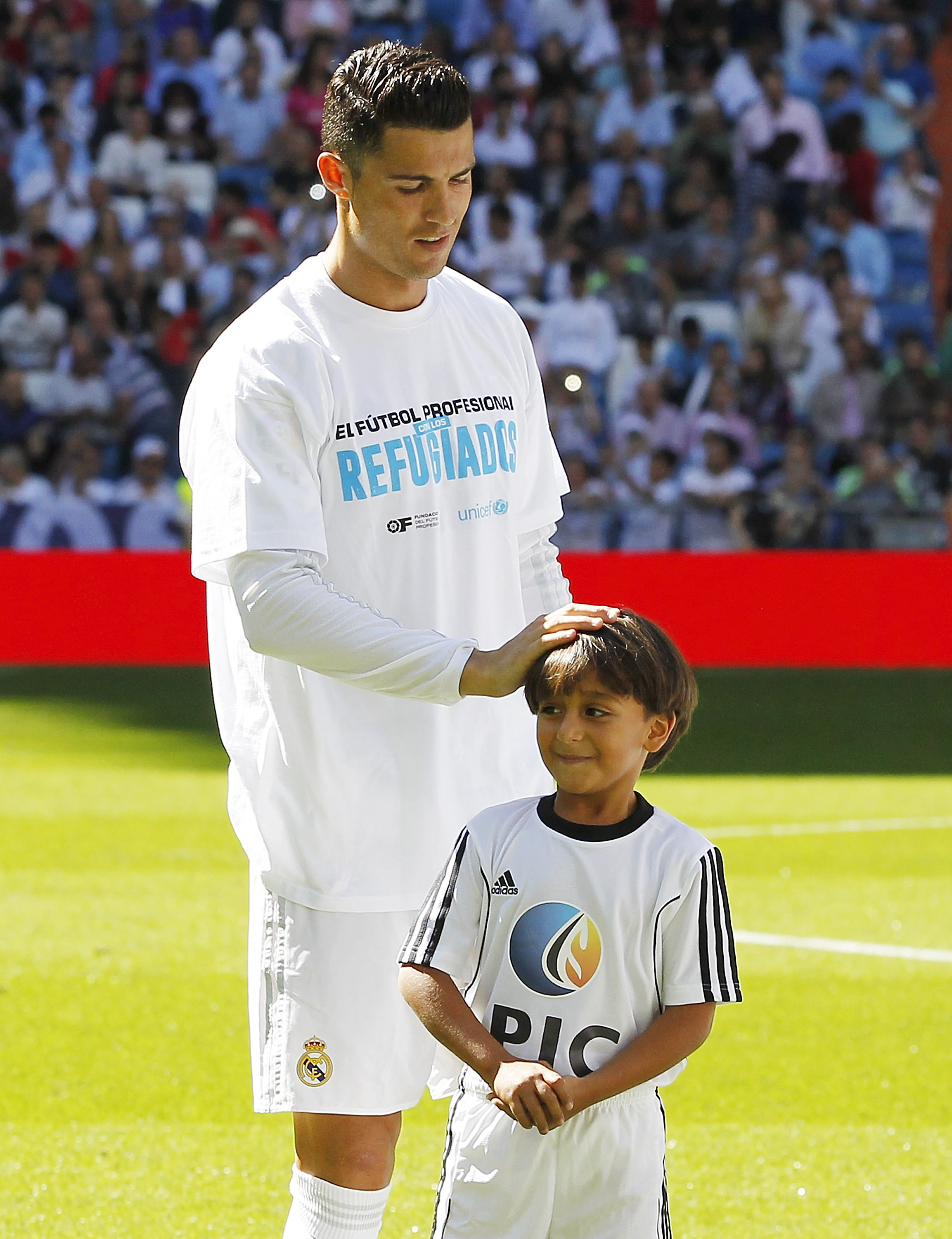 Zaid, son of Osama Abdul Mohsen, the Syrian refugee who was tripped over by a Hungarian journalist, pose with Cristiano Ronaldo of Real Madrid before the La Liga match between Real Madrid CF and Granada CF at Estadio Santiago Bernabeu on Sept. 19, 2015 in Madrid, Spain.