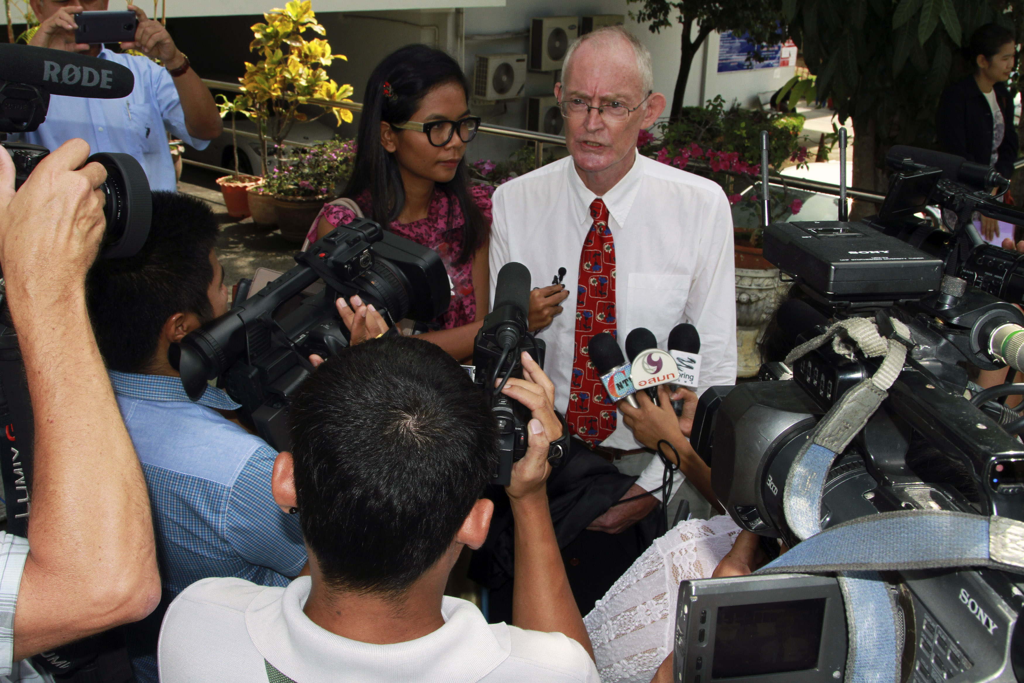Phuketwan journalists Alan Morison, right, and Chutima Sidasathian speak to media as they arrive to a criminal court in Phuket on April 17, 2014