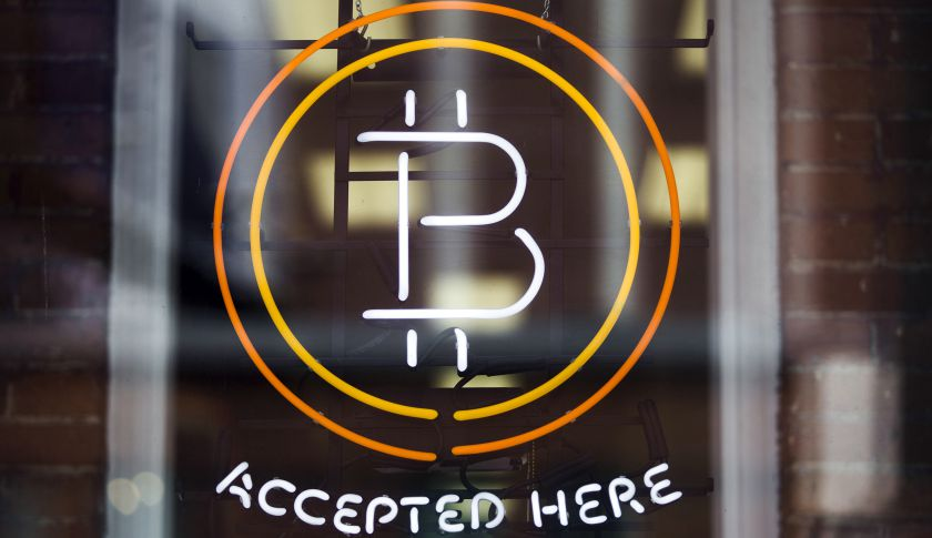 A Bitcoin sign is seen in a window.