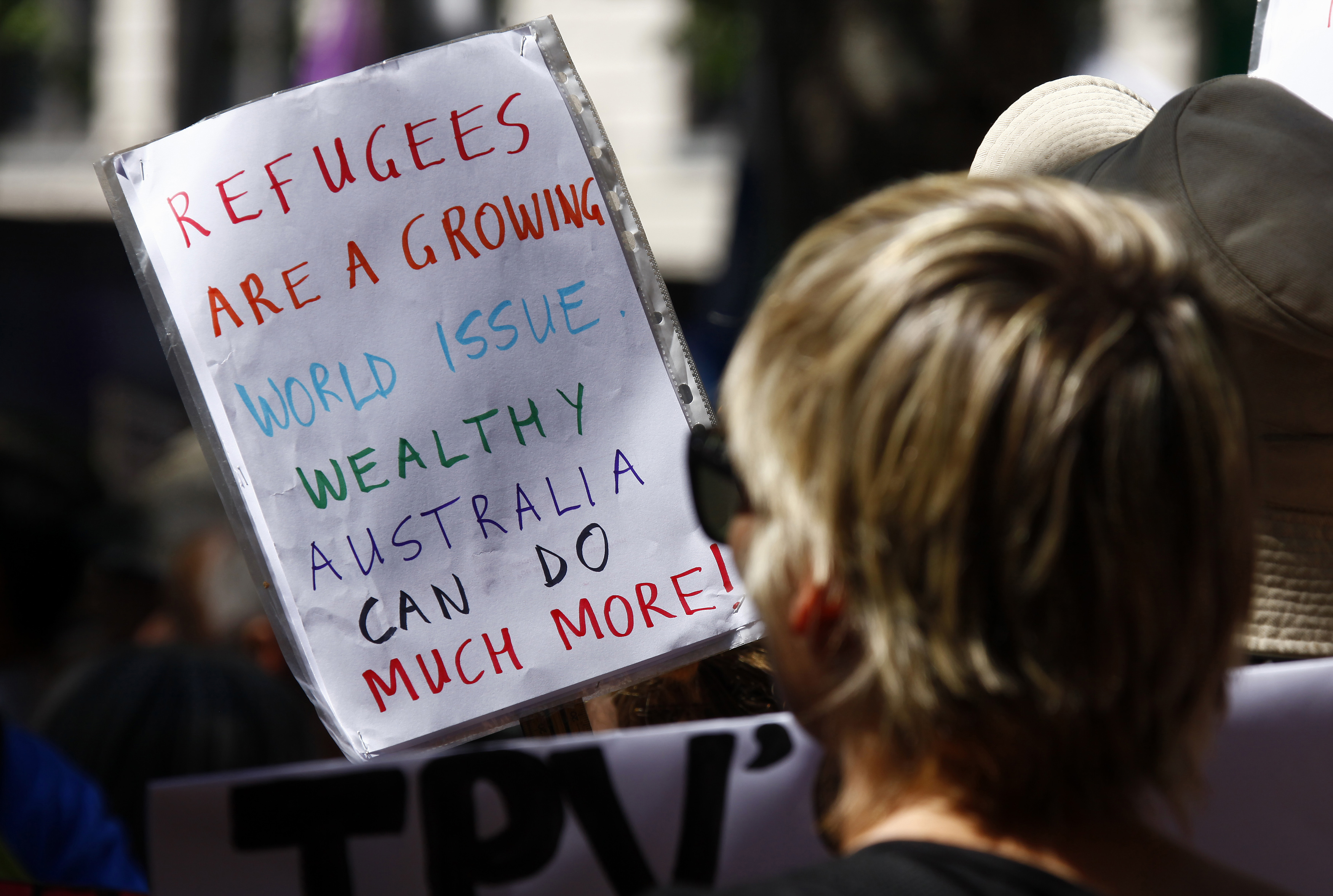 Protesters hold placards at the Stand up for Refugees rally held in central Sydney on Oct. 11, 2014