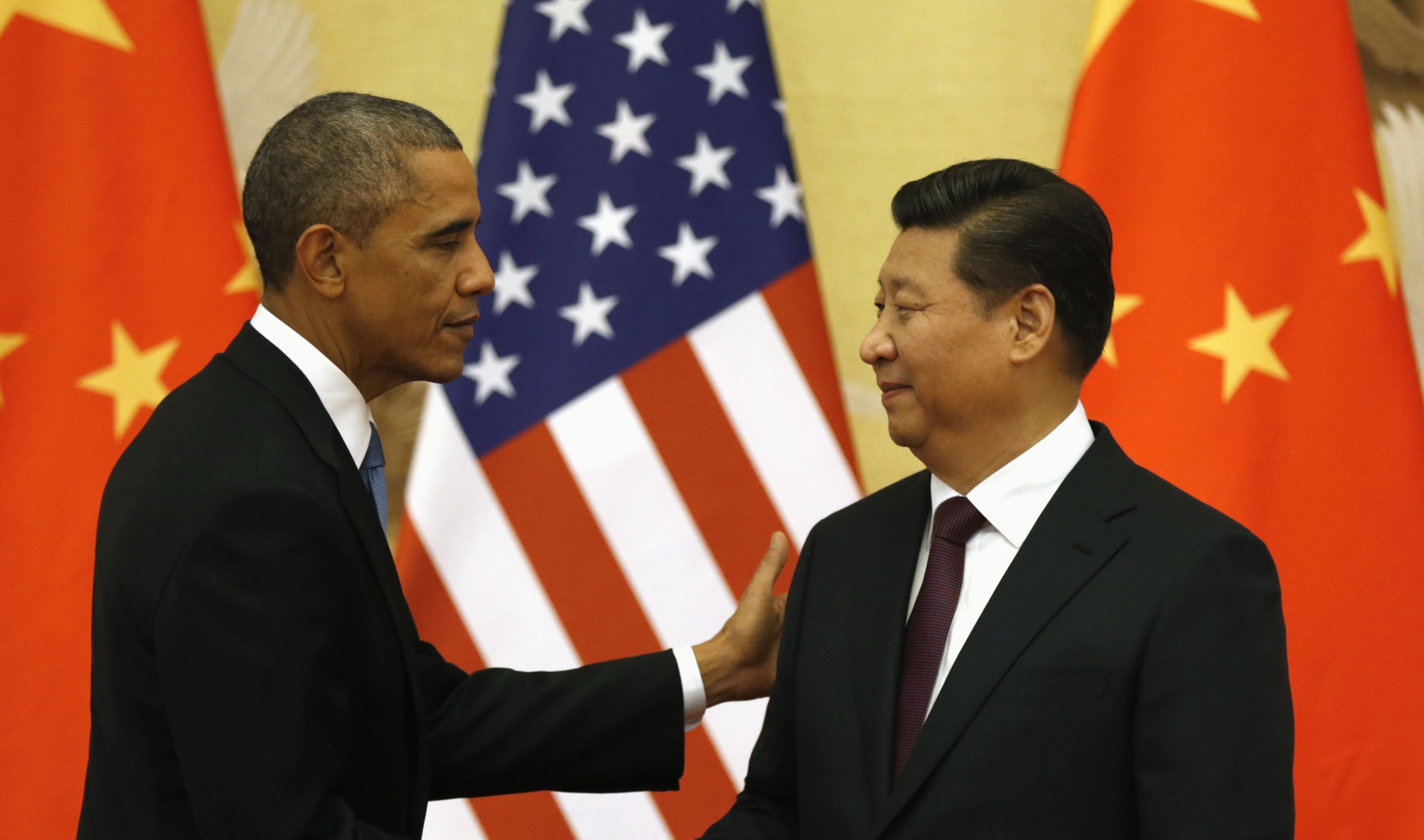 U.S. President Barack Obama pats Chinese President Xi Jinping on the shoulder at the end of their news conference in the Great Hall of the People in Beijing on Nov. 12, 2014