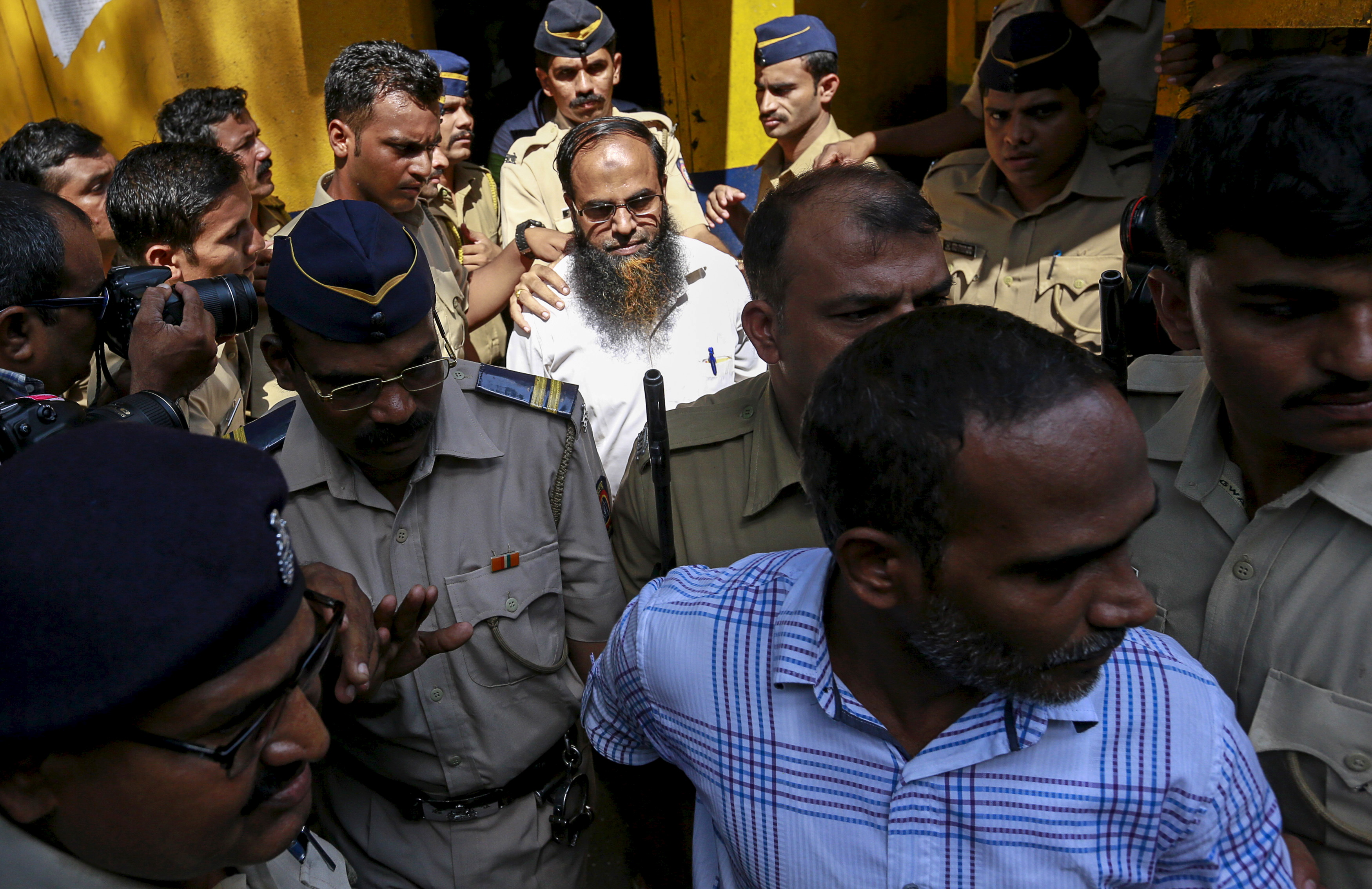 Two of the 12 men, convicted of planning several blasts on crowded commuter trains in the financial capital of Mumbai in 2006, are escorted by police to a court in Mumbai, India,