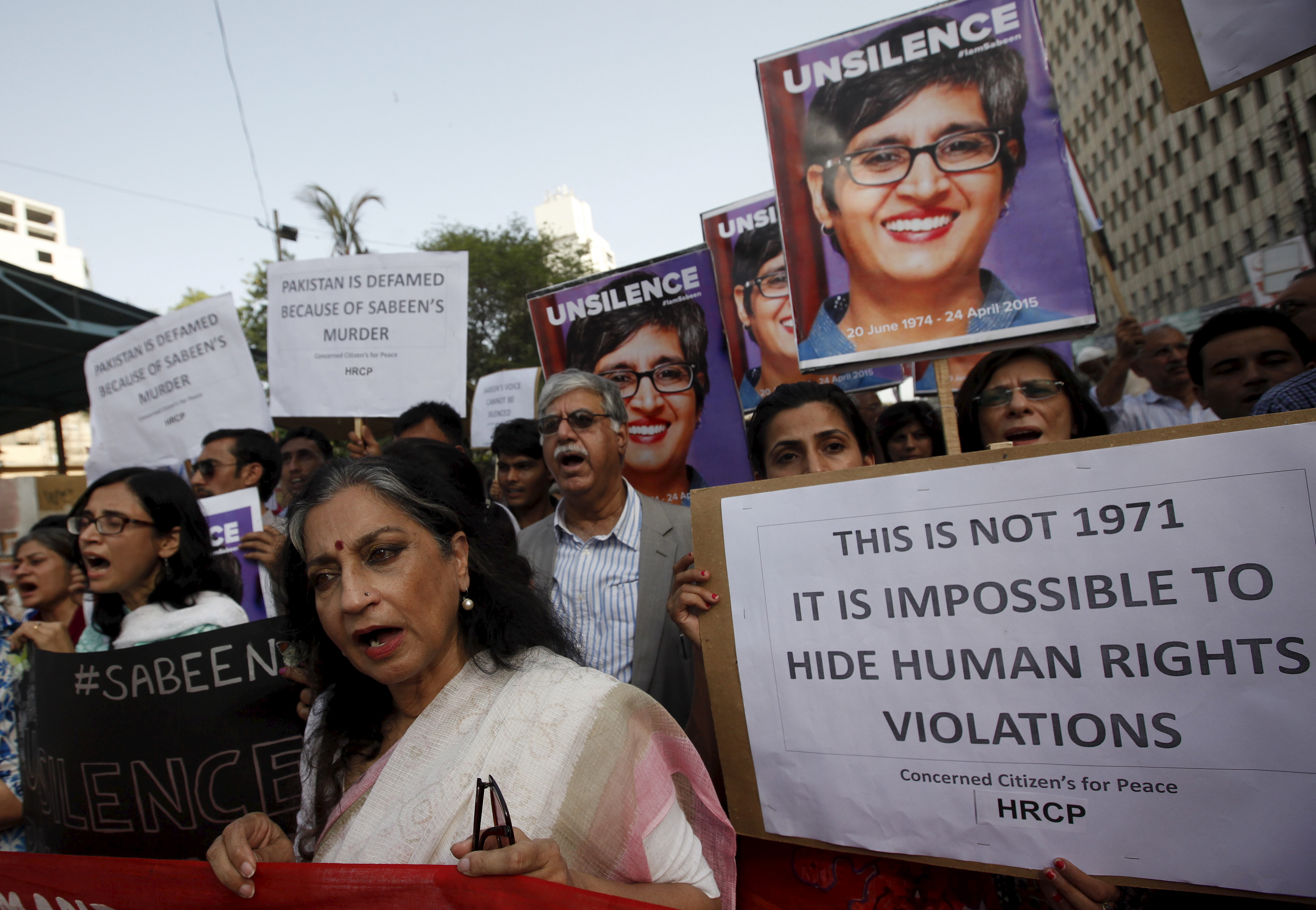 People chant slogans as they hold signs and pictures of Sabeen Mahmud, a human rights activist who was shot by gunmen, during a protest demanding justice outside the Press Club in  Karachi, Pakistan, April 30, 2015.