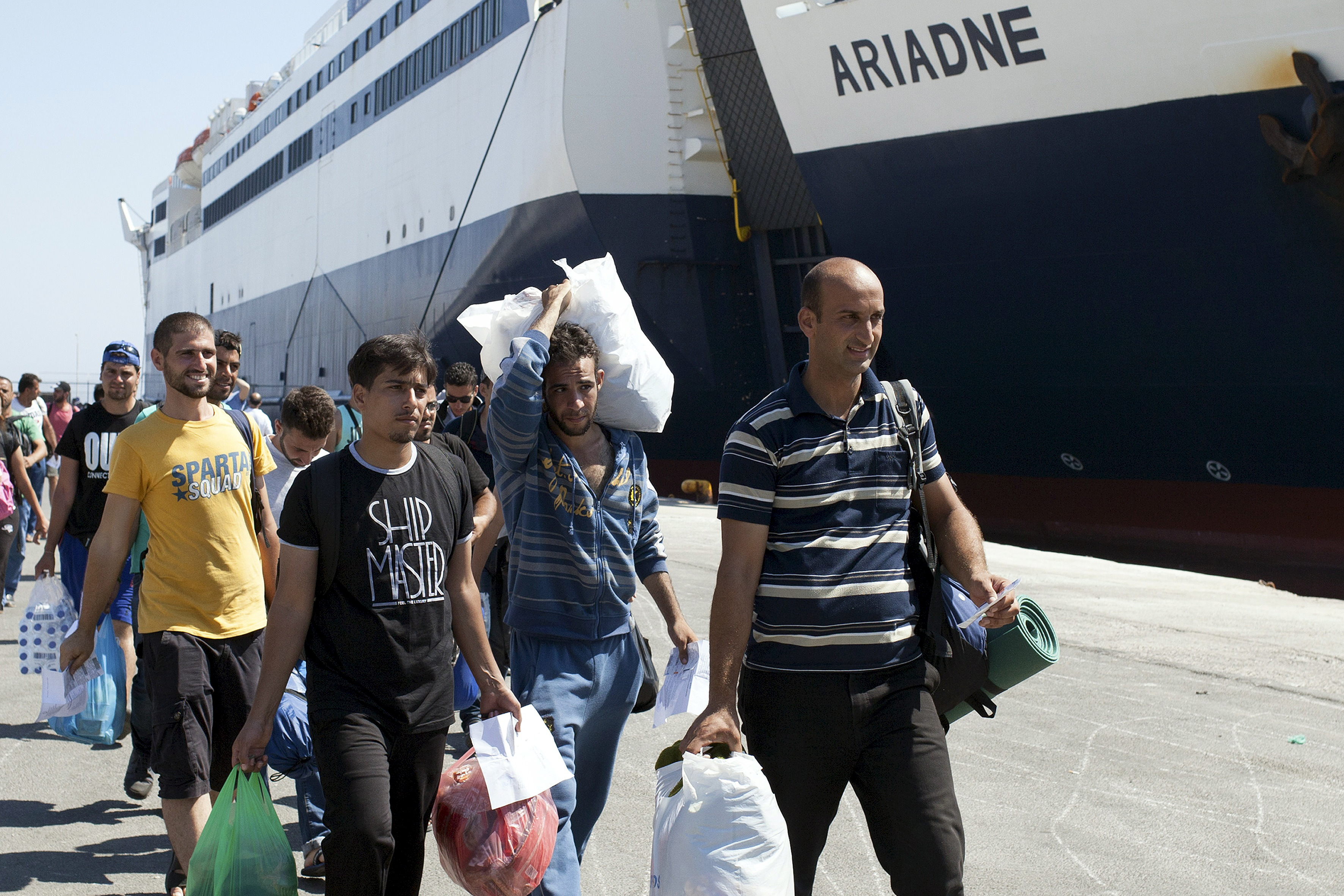 Refugees and migrants carry their belongings while boarding the passenger ship Tera Jet heading to the port of Piraeus, on the Greek island of Lesbos, on Sept. 1, 2015