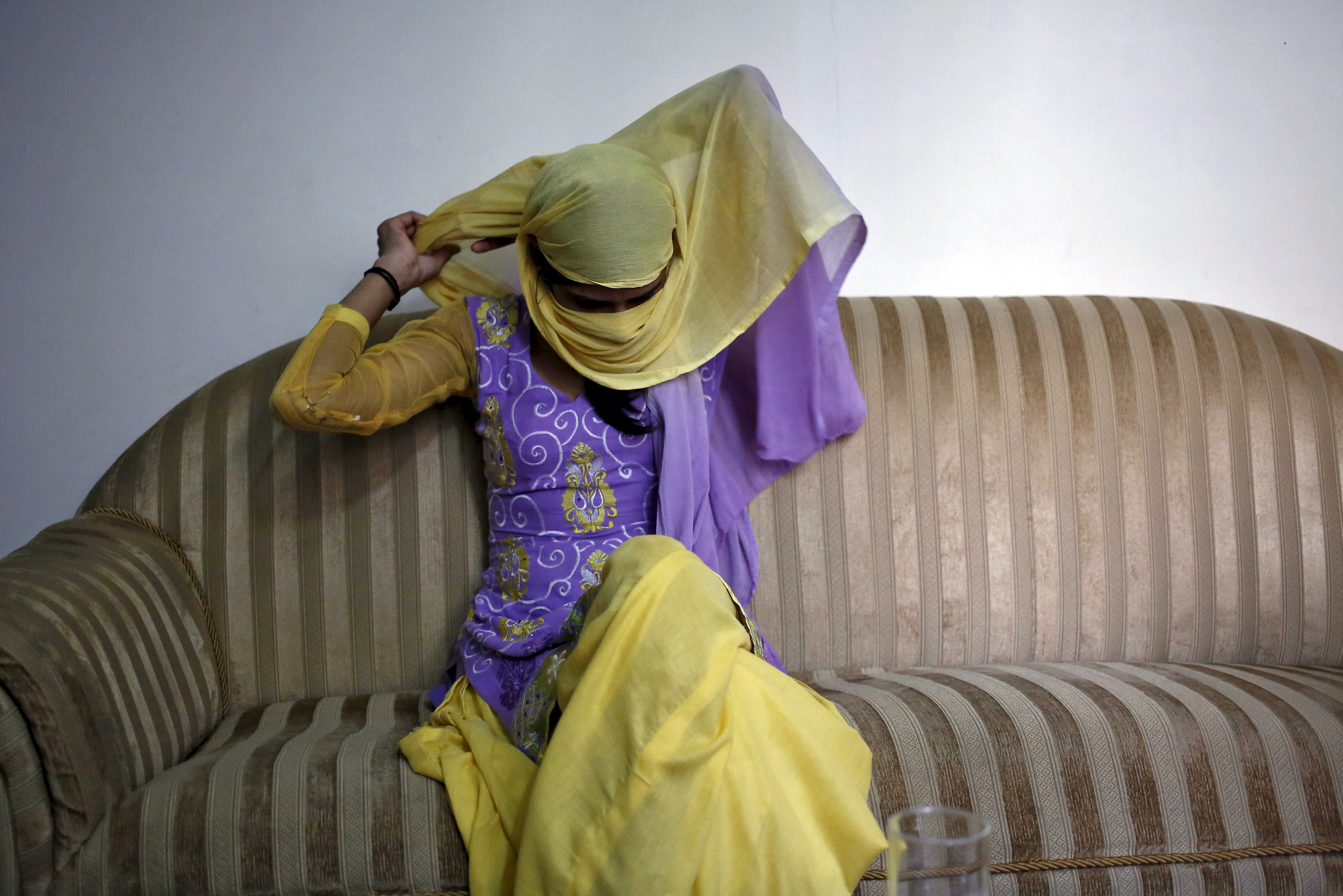 Meenakshi Kumari, 23, one of the two sisters allegedly threatened with rape by a village council in the northern Indian state of Uttar Pradesh, adjusts her headgear as she sits inside her lawyer's chamber in New Delhi on Sept. 1, 2015