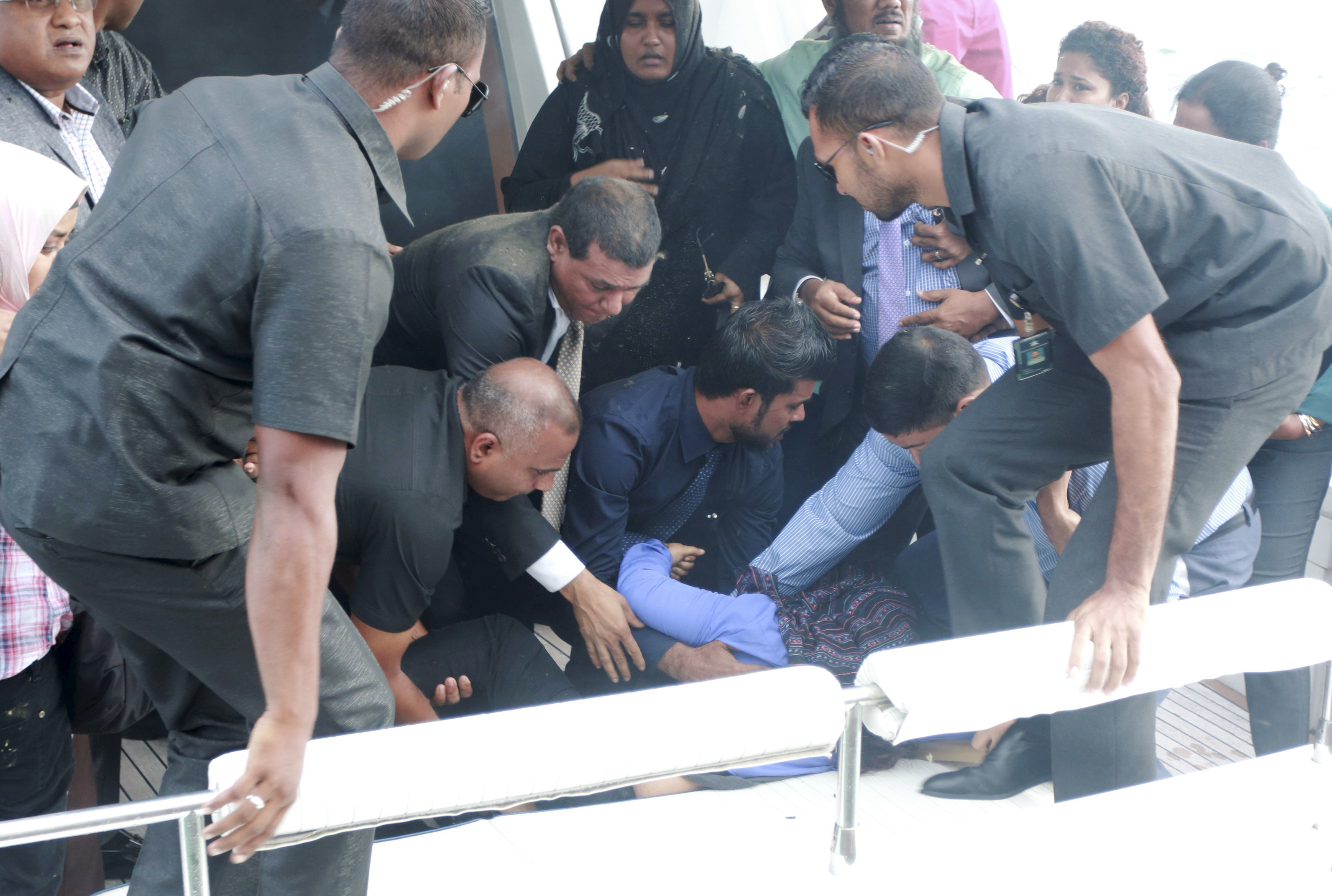 Officials carry an injured woman off the speed boat of Maldives President Abdulla Yameen (not pictured) after an explosion onboard, in Male, Maldives September 28, 2015.