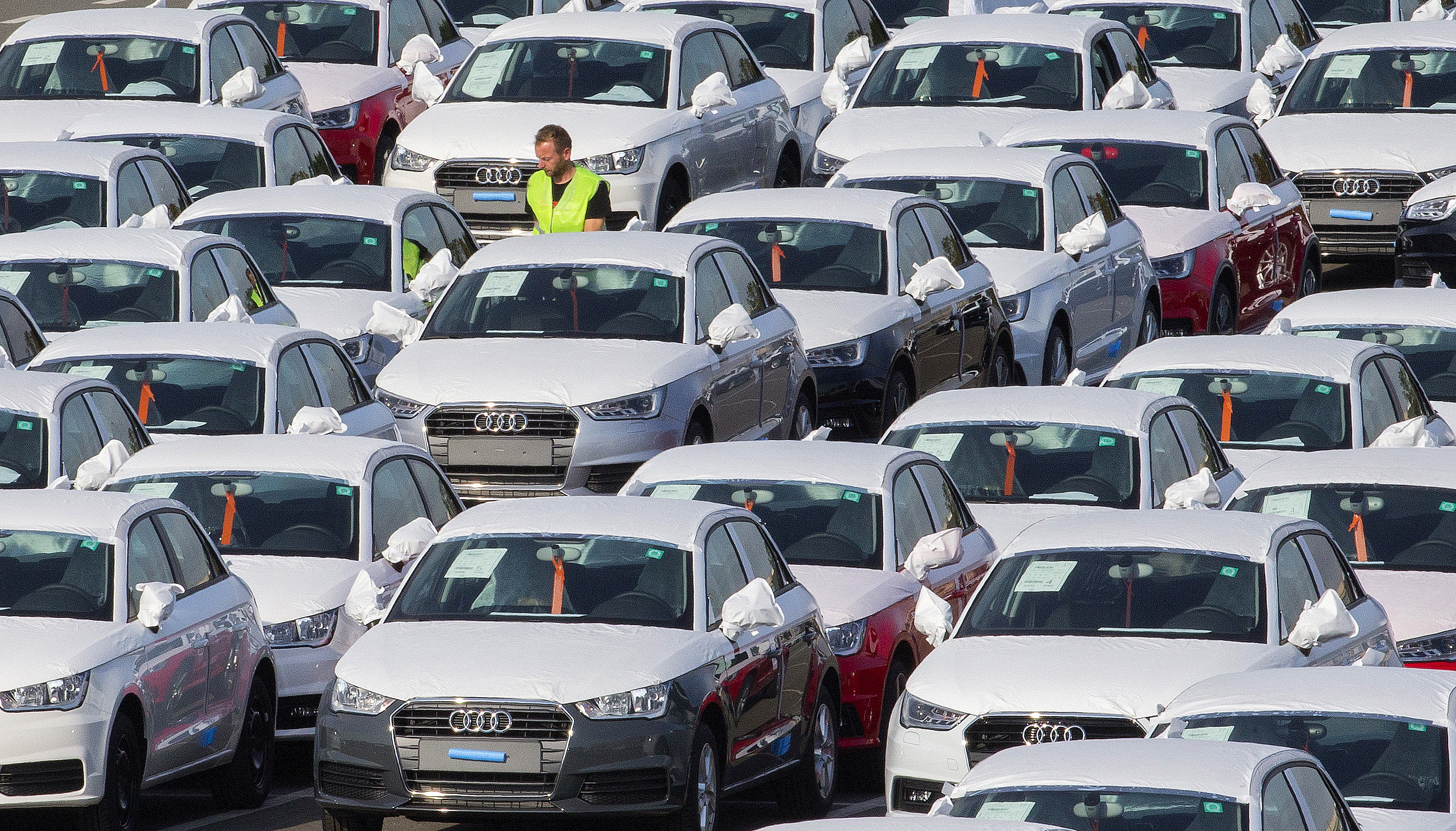 A worker walks among Audi A1 cars in the parking of the Audi powerplant in Brussels, Belgium September 28, 2015.