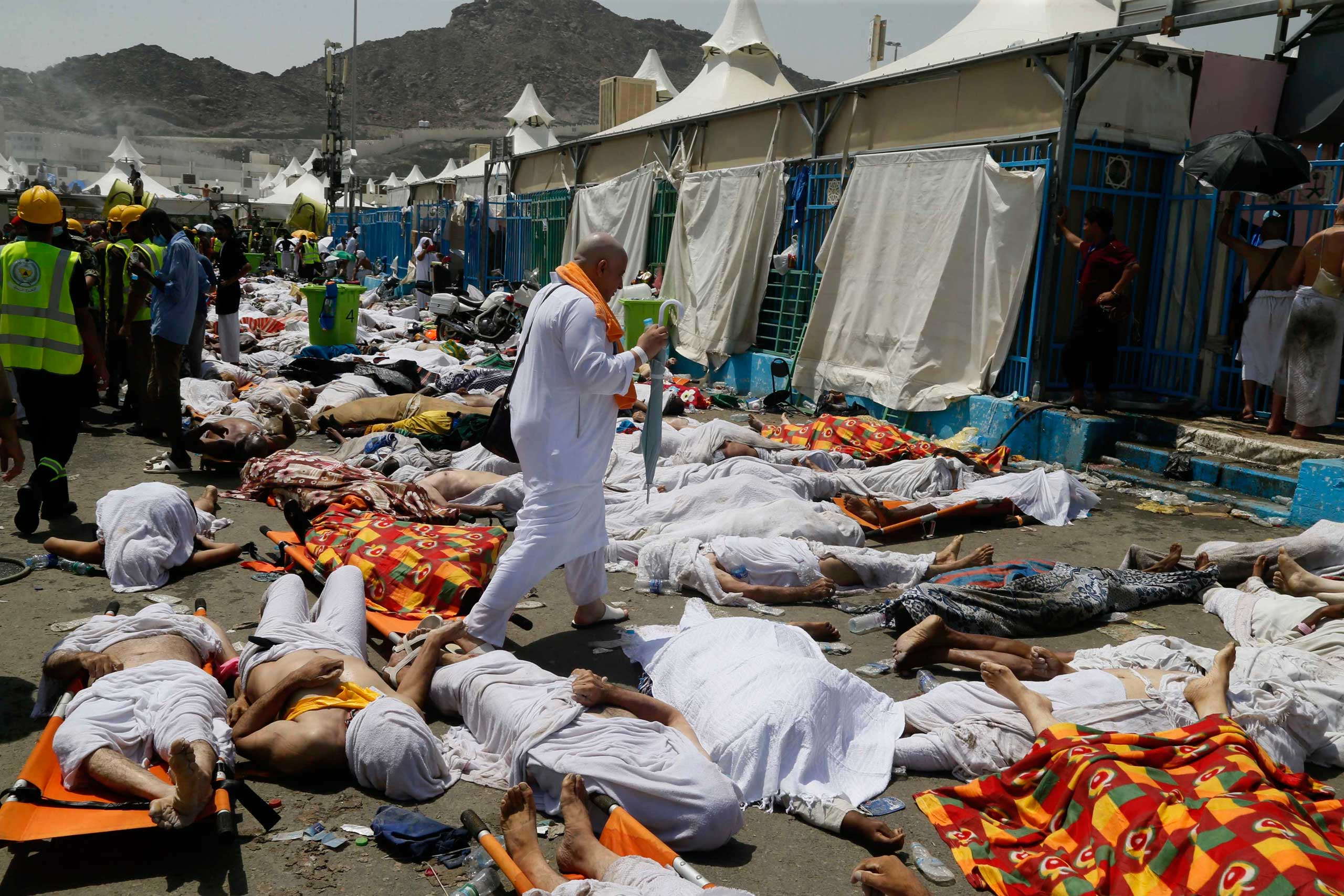 A muslim pilgrim walks through the site where the victims of a stampede are gathered in Mina, Saudi Arabia during the annual hajj pilgrimage on Sept. 24, 2015.